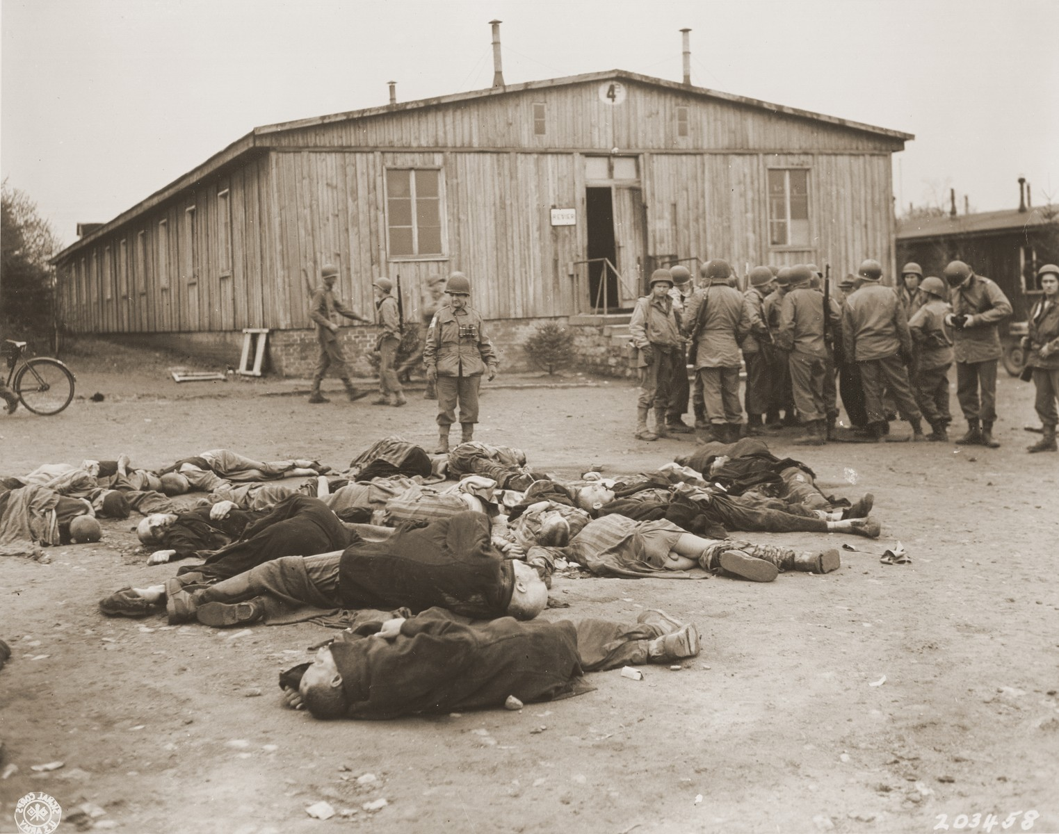 American soldiers view the bodies of prisoners that lie strewn on the ground in the newly liberated Ohrdruf concentration camp.