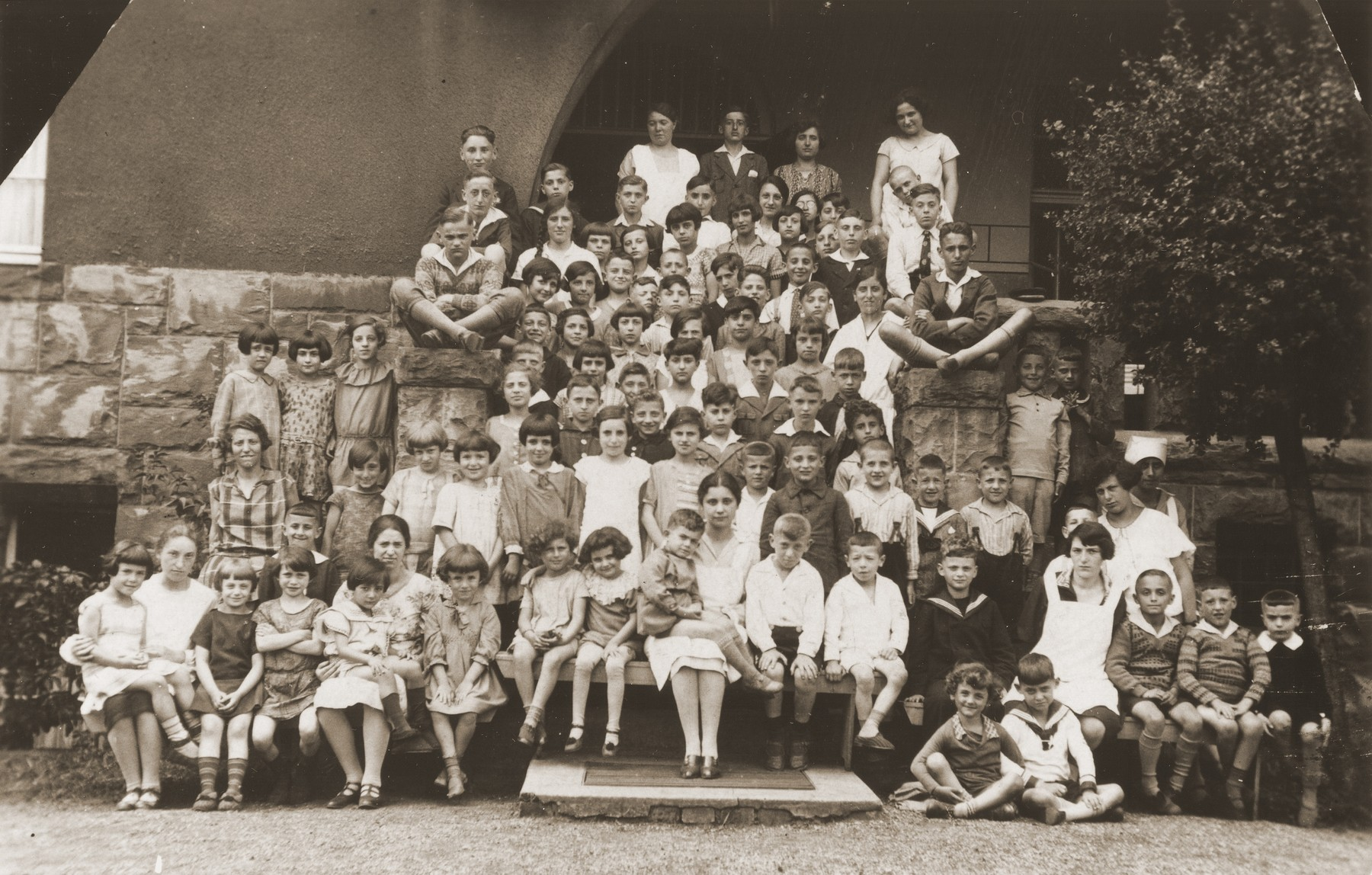 Group portrait of children at a Jewish summer camp.    Pictured in the center is Gerd Zwienicki.  In front of him is Hannah Steinberg.