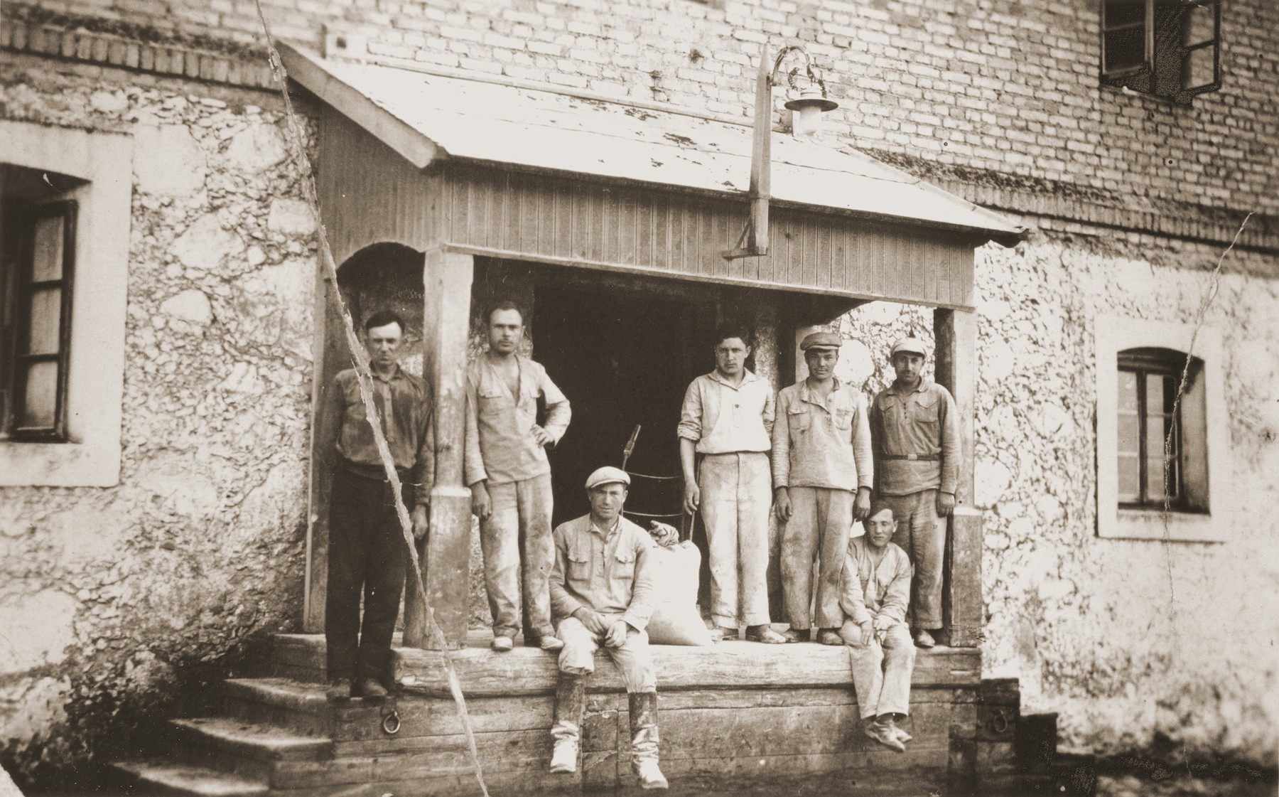 Jewish workers pose on the porch of a mill in Lyubcha.
