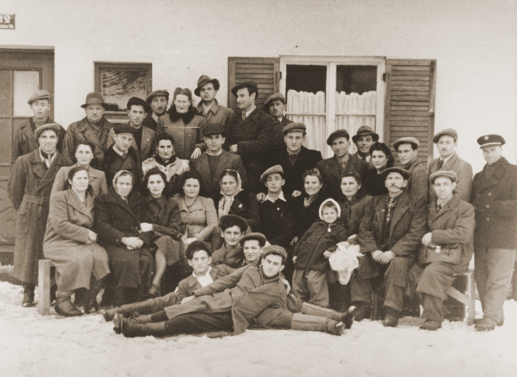 Group portrait of former Bielski partisans from Nowogrodek taken in the Foehrenwald displaced persons camp.  Idel Kagan is in the center of the pyramid in the front.  Anna (Hendel Duszkin) is seated in the front row, fourth women from the left.  Chaya Bielski is seated third from the left.  Her mother is to her left.  Abramele Intersky is standing second from left.  Taibel nee Bielski is seated third from the right.  Joseph Skakun is standing in the center.  Ida (Chayka) Zelwin (Zelvianski) in the last row fifth from the left with the coat with the fur collar. Her husband, Sam Zelwin(Zelvianski) is the last person on the right in the last row.
