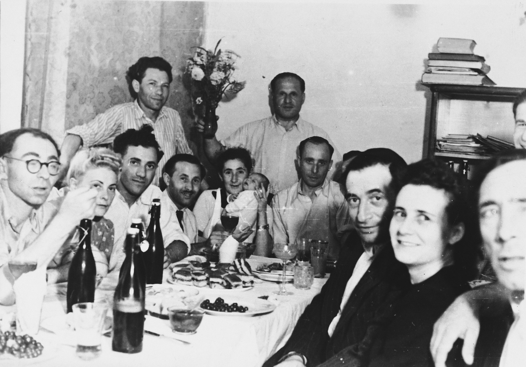 Jewish displaced persons gather around a table for a celebration in the Lampertheim DP camp.