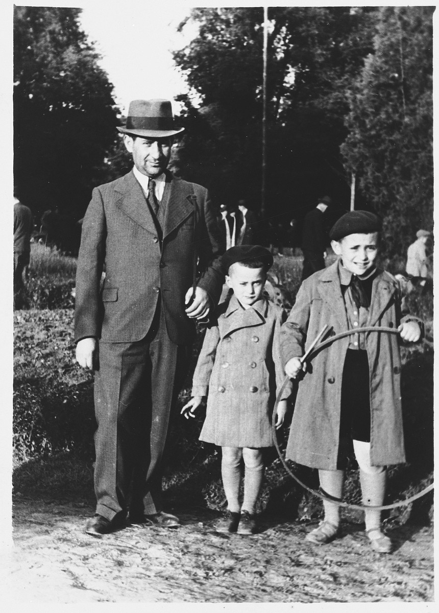 Isaac Friedberg poses outside with his two sons, Maurice (right) an Shimon (center).
