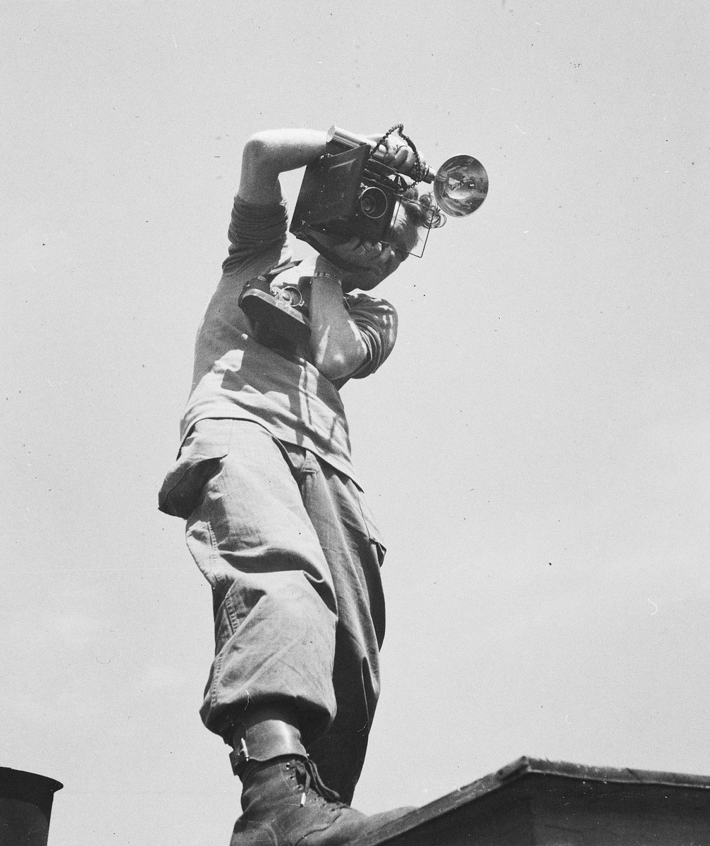A U.S. army combat photographer, Walter D. MacDonald, takes a picture with a Speed Graphic camera from the roof of a building.