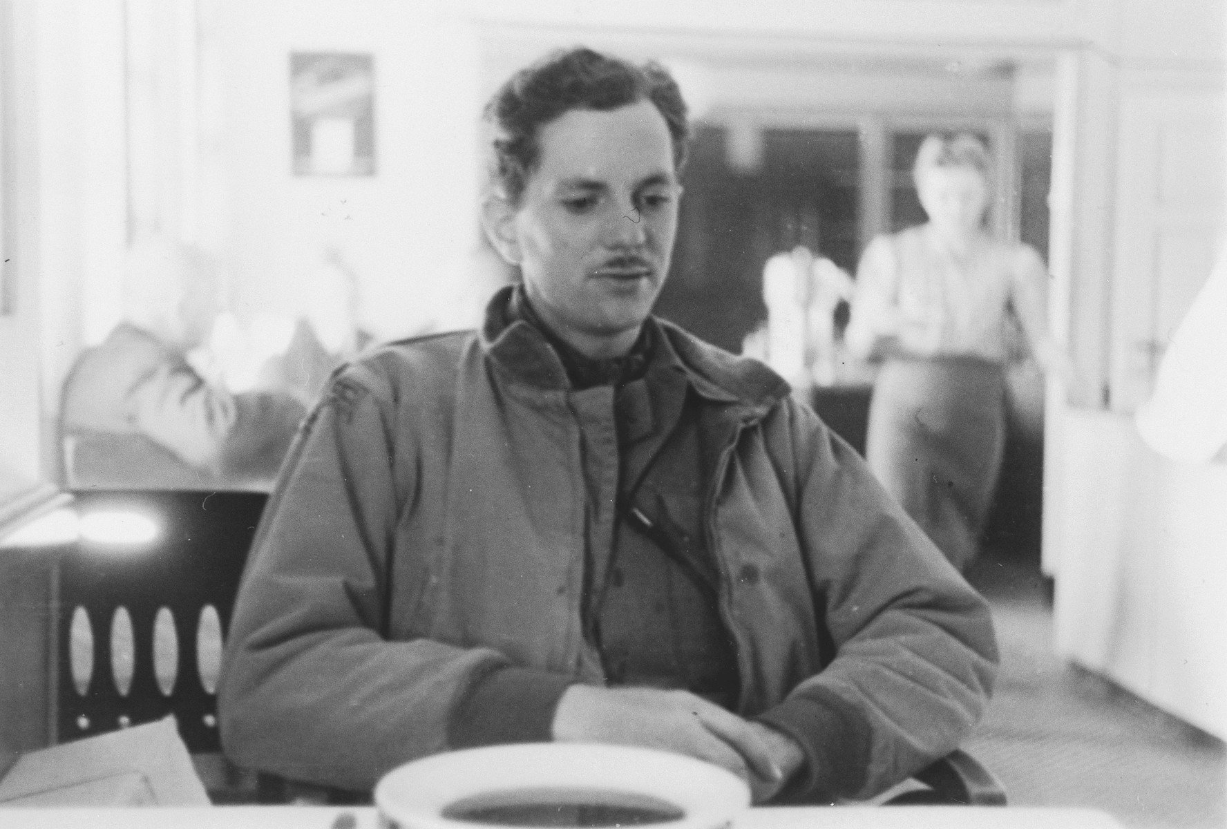 Portrait of U.S. combat photographer Arnold E. Samuelson seated in a dining hall with a bowl of soup.