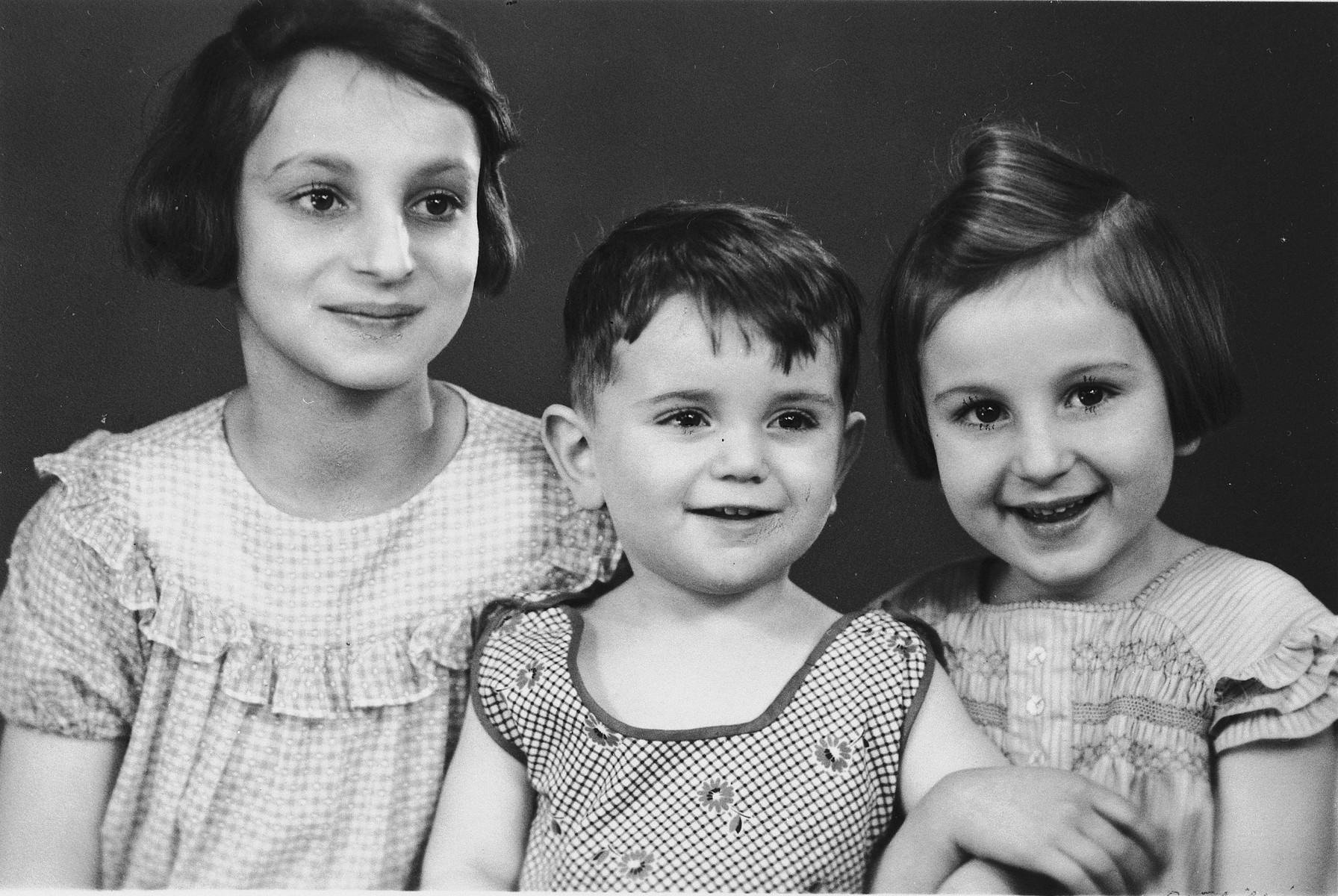 Studio portrait of three Jewish children in Cologne, Germany.  Pictured from left to right are: Inge, Egon and Gisela Berg.  Egon was the cousin of Inge and Gisela and the son of Karl and Rosel (Marx) Berg from Cologne.