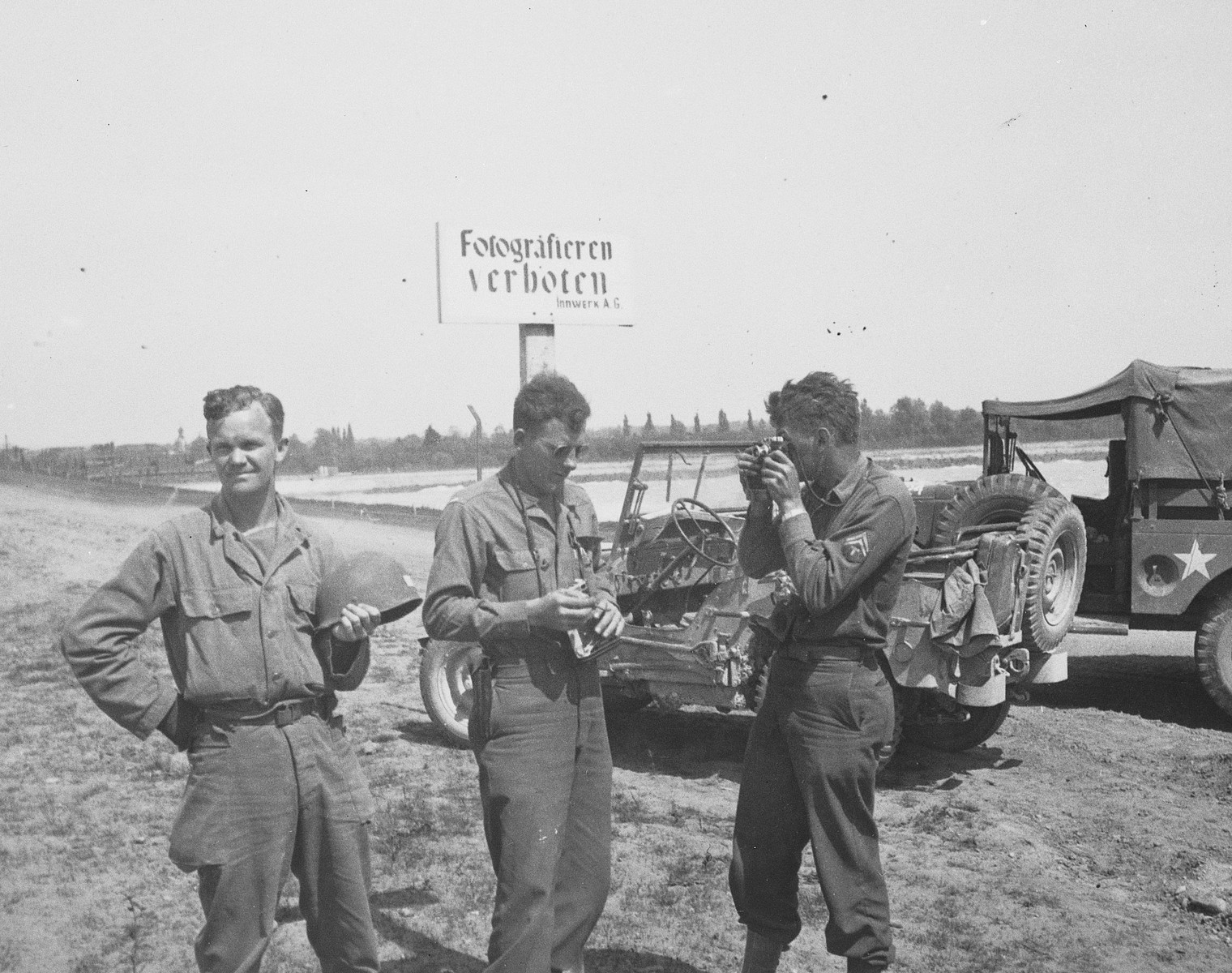 """Three U.S. combat photographers from the 167th Signal Photo Company stop to take pictures in front of a German sign that reads, """"Photography is prohibited.""""  Pictured on the left is Walt MacDonald."""