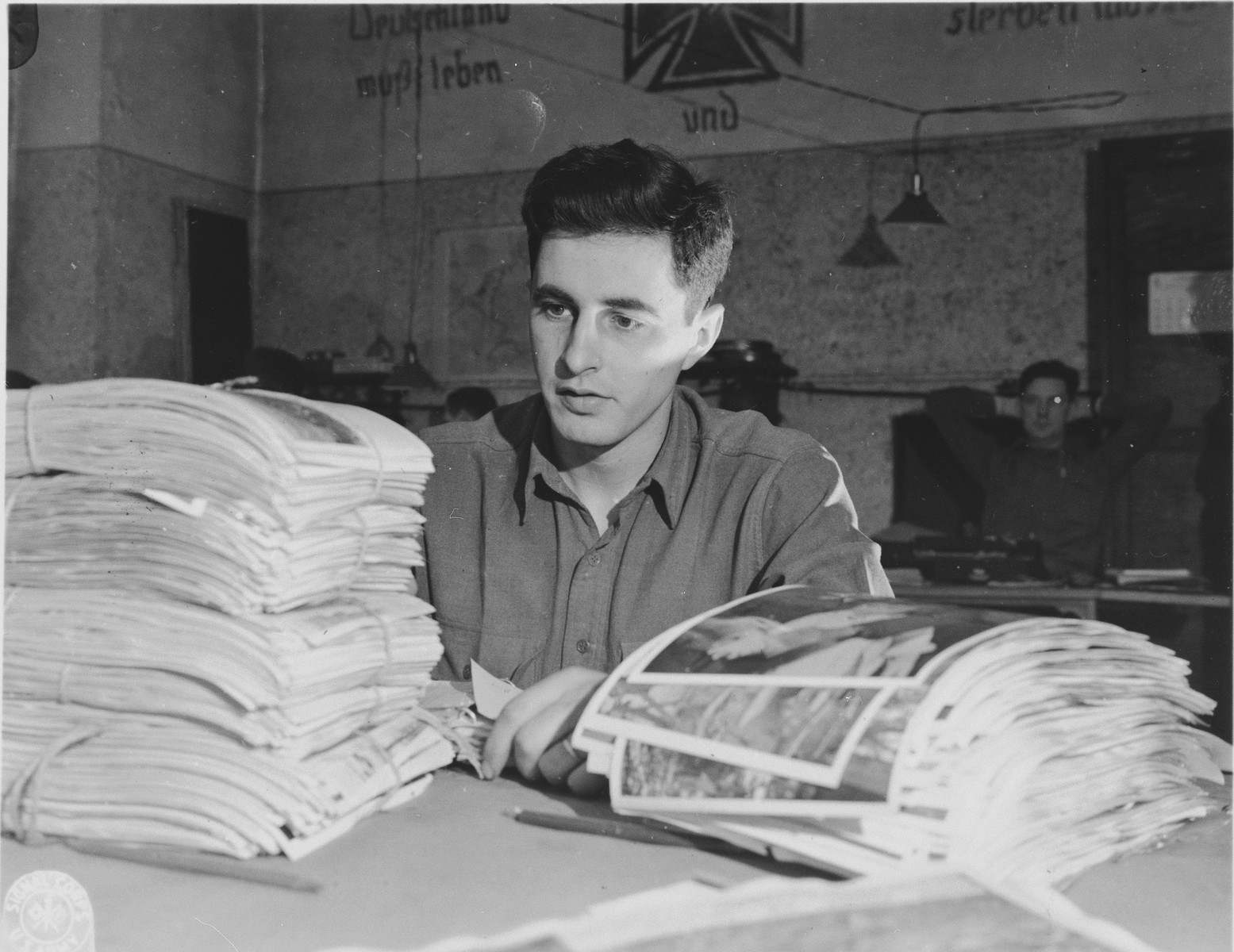 U.S. army photographer John O'Brien reviews a stack of Signal Corps photographs.