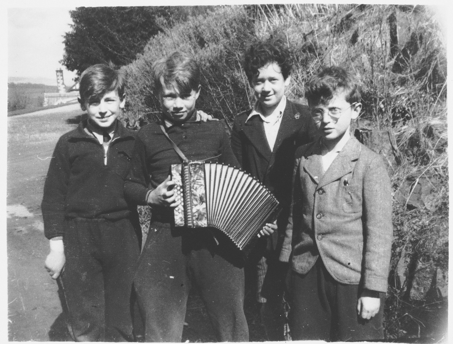 Portrait of four boys, one of whom is playing the accordian, in the Priory, a children's home in Selkirk Scotland.  Pictured are Henri Zang (Germany), Max Spiro (Hamm,Germany), Egon Drab (Vienna), and Kurt Deutsch (Ash, Czechoslovakia).  Netta Pringle, the assistant matron in the Priory, formed warm relations with many of the twenty-one Jewish children.  She took most of the photographs, which she assembled in the album and wrote the inscriptions.  In 1996 Miss Pringle gave the album to Gunther.