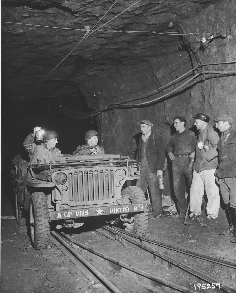Two U.S. combat photographers from the 167th Signal Photo Company are greeted by four French miners during their investigation of the Burca iron mine that was thought to have been the site of a German bomb factory.