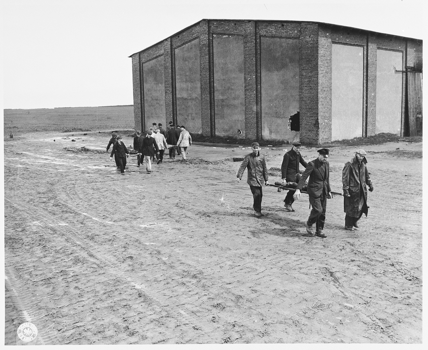 German civilians carry corpses on stretchers to be buried in mass graves.  The victims are concentration camp prisoners who were killed by the SS in a barn, shown in the background, just outside Gardelegen.