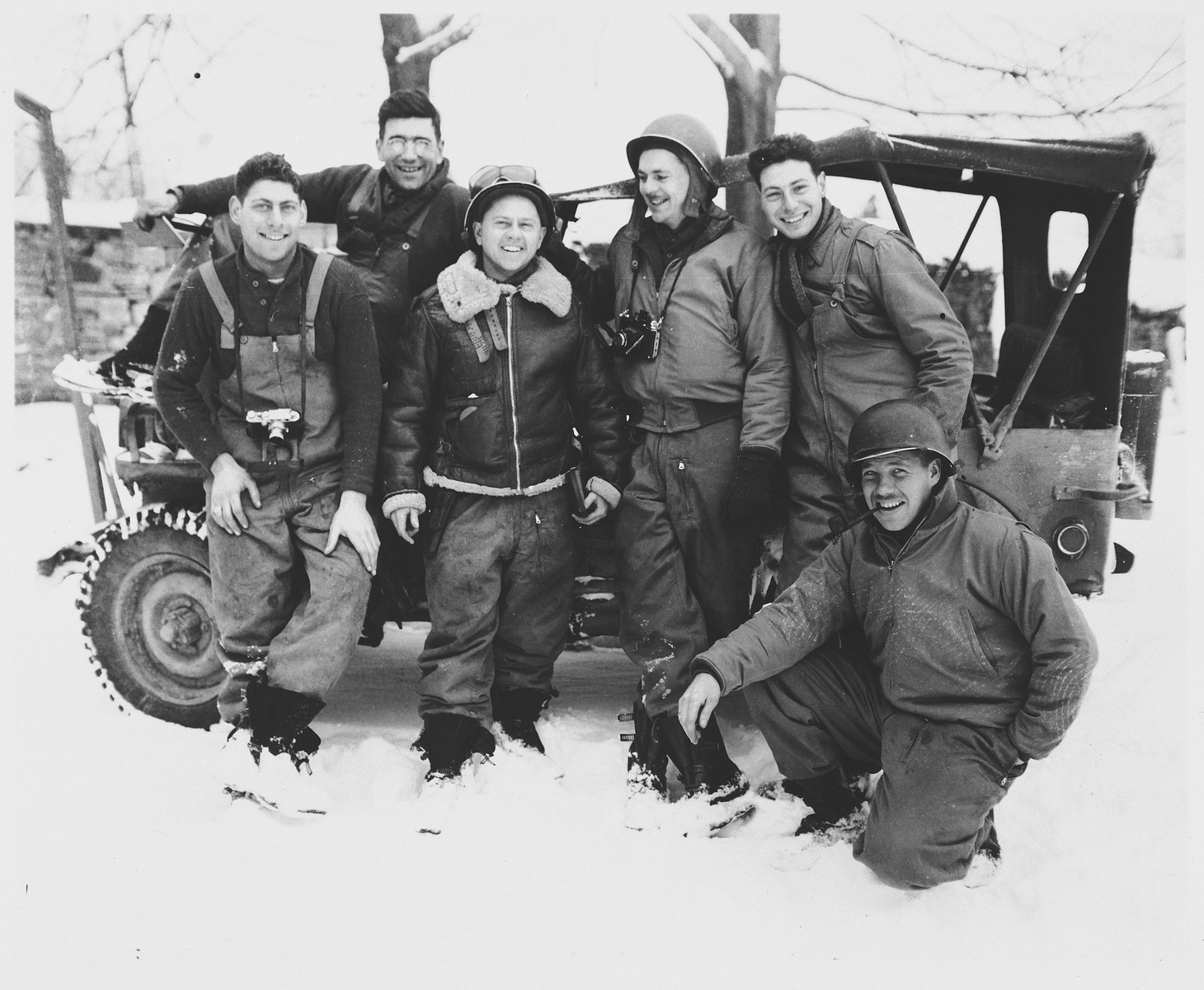 Actor Mickey Rooney poses with the U.S. combat photographers from the 167th Signal Photo Company during his visit to the ETO (European Theatre of Operations).  Pictured from left to right are: Charles Tesser, Carmen Currad, Mickey Rooney, Arnold Samuelson, Eliot Finkels and John C. Perry (kneeling).
