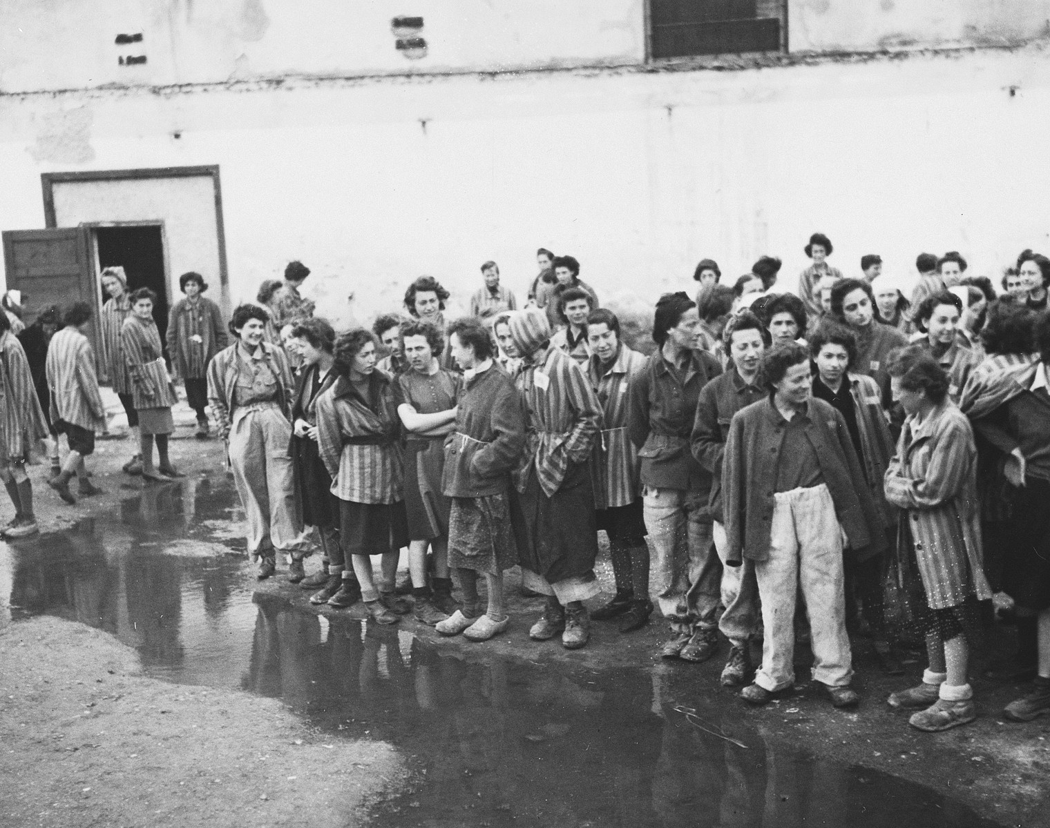 Female survivors gather outside a barracks in the newly liberated Lenzing concentration camp.