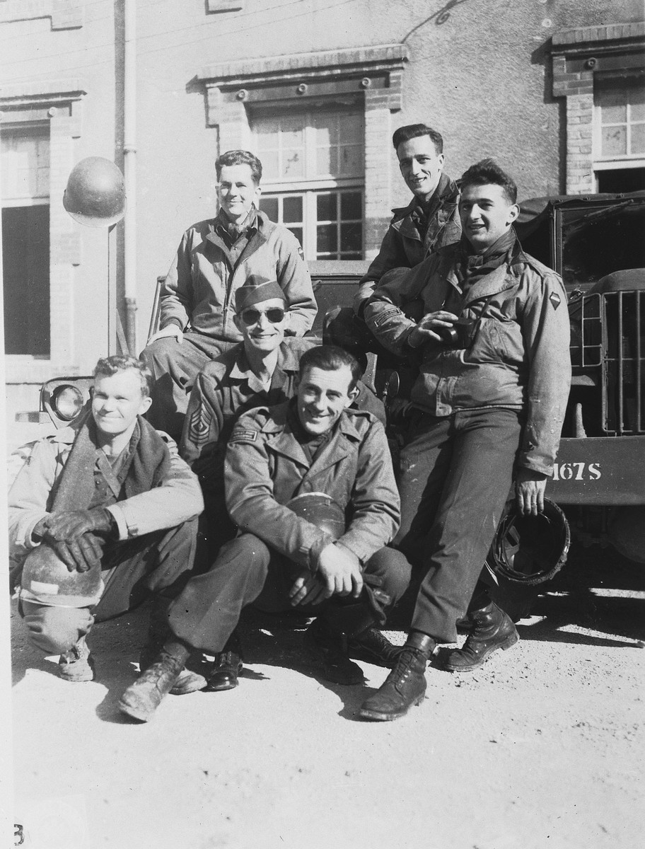 Group portrait of members of Combat Unit 123, a unit of the U.S. Army 167th Signal Photo Company.  Pictured in front from left to right are: Walt MacDonald and Eddie Urban.  In the middle is Gene Coogan; at the right is J Malan Heslop; behind from left to right are Arnold Samuelson and John O'Brien.