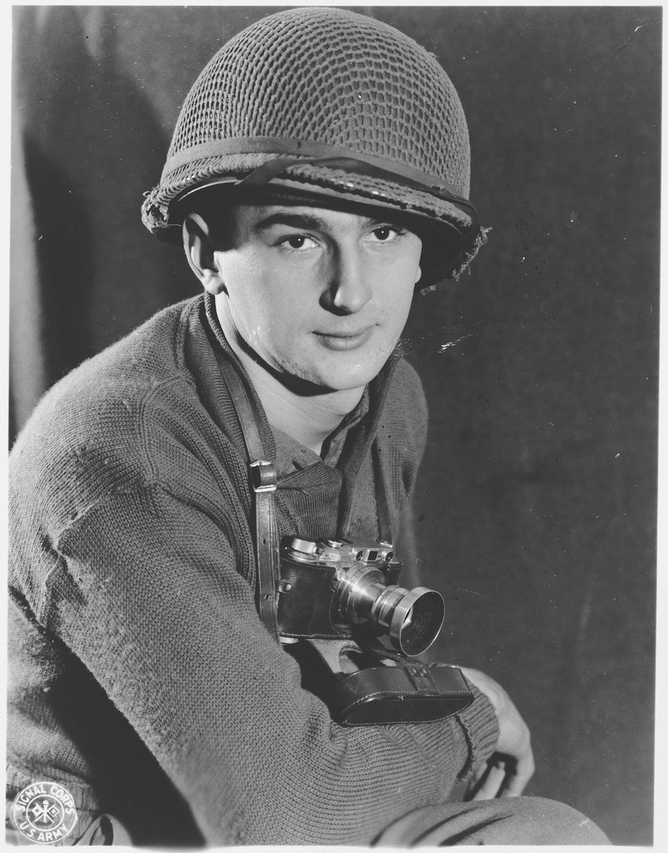 Portrait of U.S. combat photographer J Malan Heslop wearing a camera around his neck.