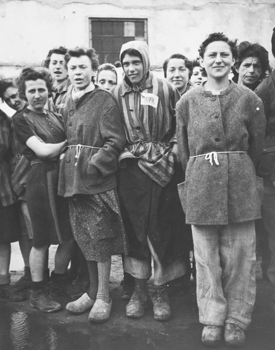 A group of female survivors stands outside a barracks in the newly liberated Lenzing concentration camp.