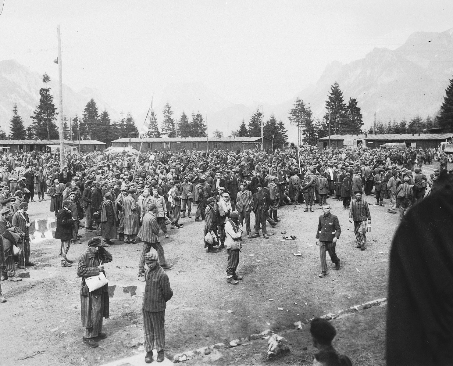 A crowd of survivors gathers in the main square of the newly liberated Ebensee concentration camp.  The group at the left waves an American flag.