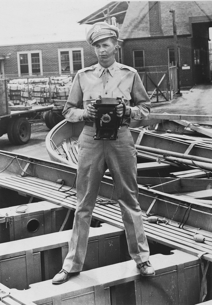 Portrait of U.S. combat photographer Arnold E. Samuelson holding a Speed Graphic camera while standing in a boat.