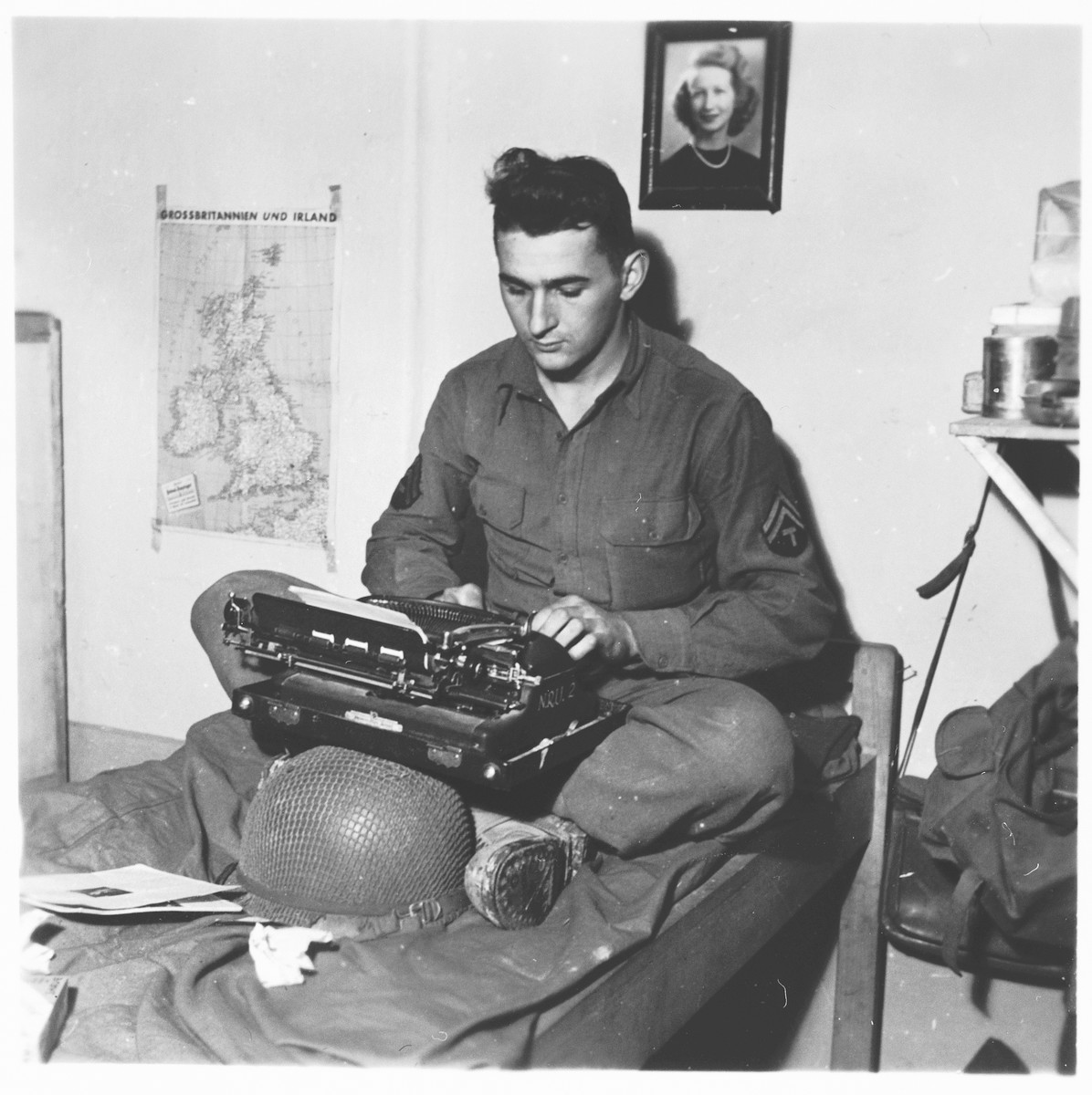U.S. combat photographer J Malan Heslop types photo captions on a typewriter in his room.