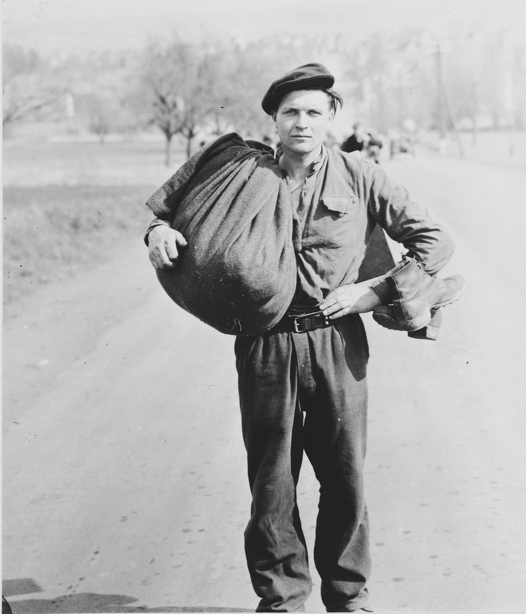 Portrait of a young, male displaced person walking with a large sack along a road in Austria at the close of World War II.