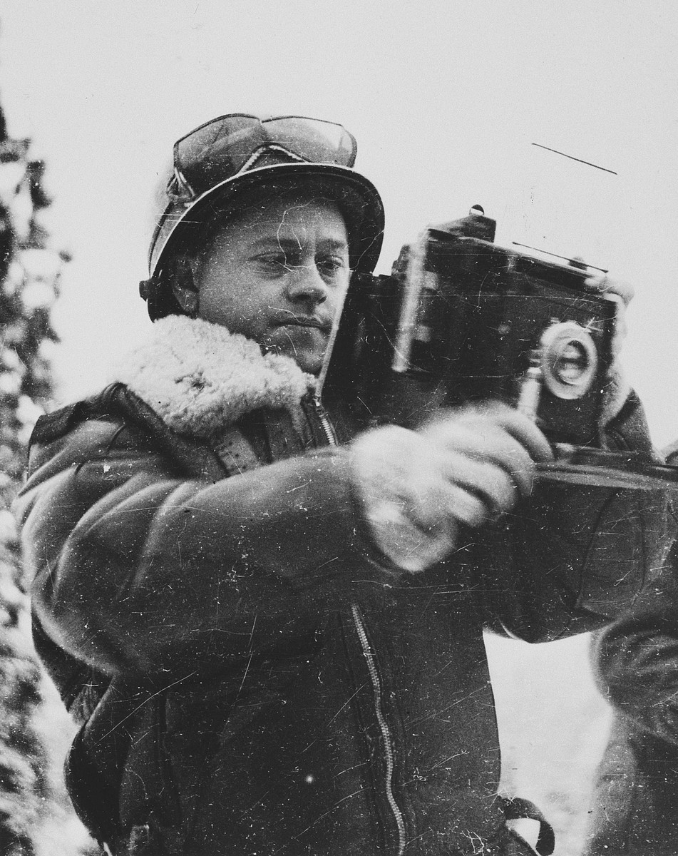 Actor Mickey Rooney poses holding a Signal Photo Company Speed Graphic camera during his visit to the ETO (European Theatre of Operations).