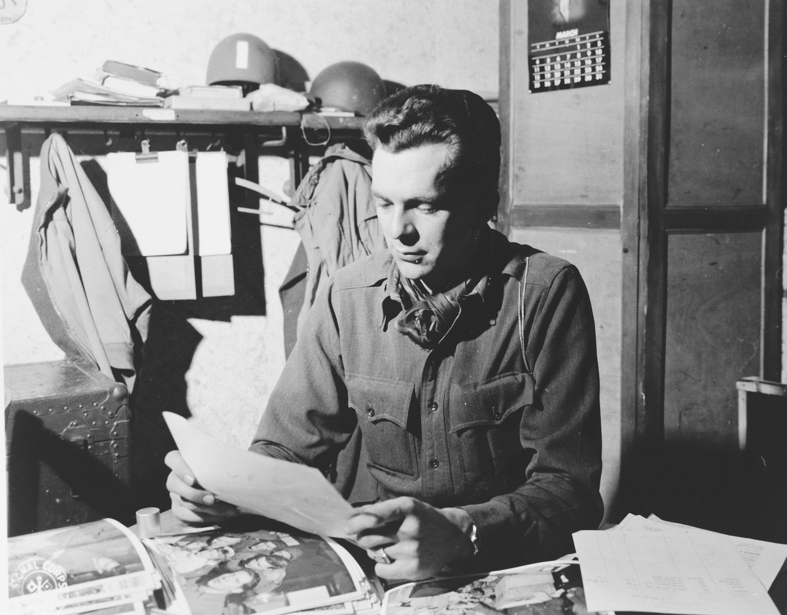 Portrait of U.S. combat photographer Arnold E. Samuelson studies a pile of photographs in his office.