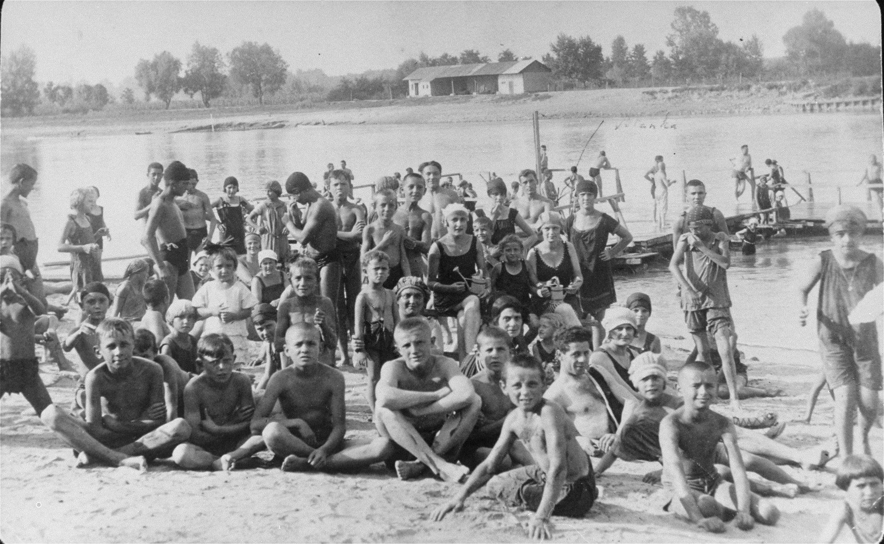 A group of young people pose on the beach.  Among those pictured is Blanka Klein (later Kupfermann). She is the girl holding a watering can, farthest to the right.