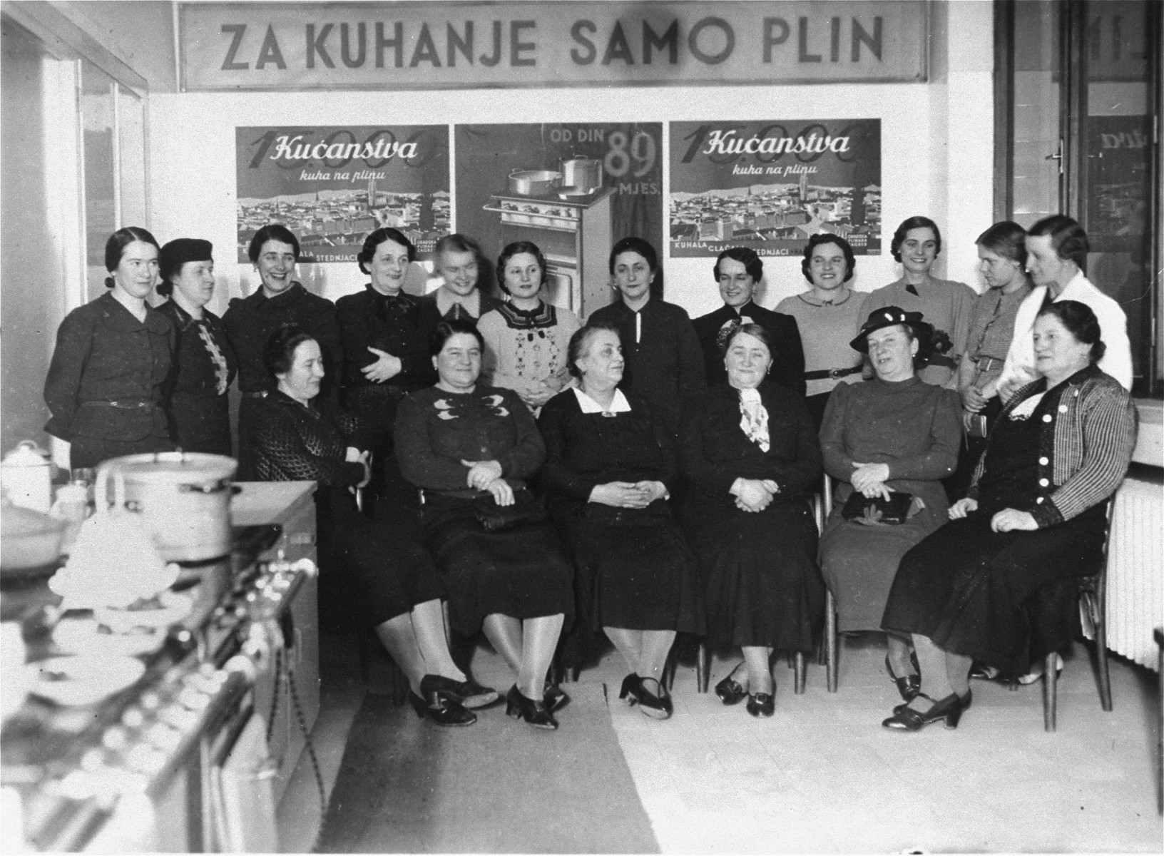 """Group portrait of women who are taking a course on gas cooking in Zagreb, Croatia.   The banner above their heads reads: """"For cooking use only gas.""""  Among those pictured is Rosa Klein (front row, third from the left), the grandmother of the donor."""