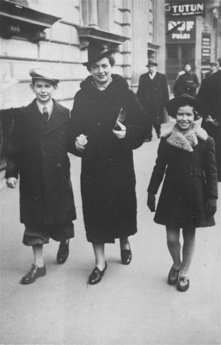 A Jewish family from Yugoslavia walks along a commercial street in Bucharest.  Pictured are Blanka Kupfermann with her two children, Aurel (left) and Marta (right).