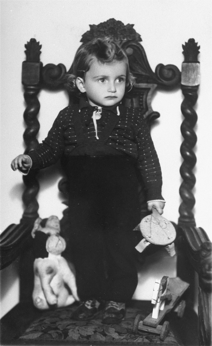 Portrait of a young Jewish boy standing on an ornate wooden armchair.  Pictured is Mladen Szego, the son of Melanka and Armin Szego.  He survived the Holocaust in hiding at a monastery in Croatia.