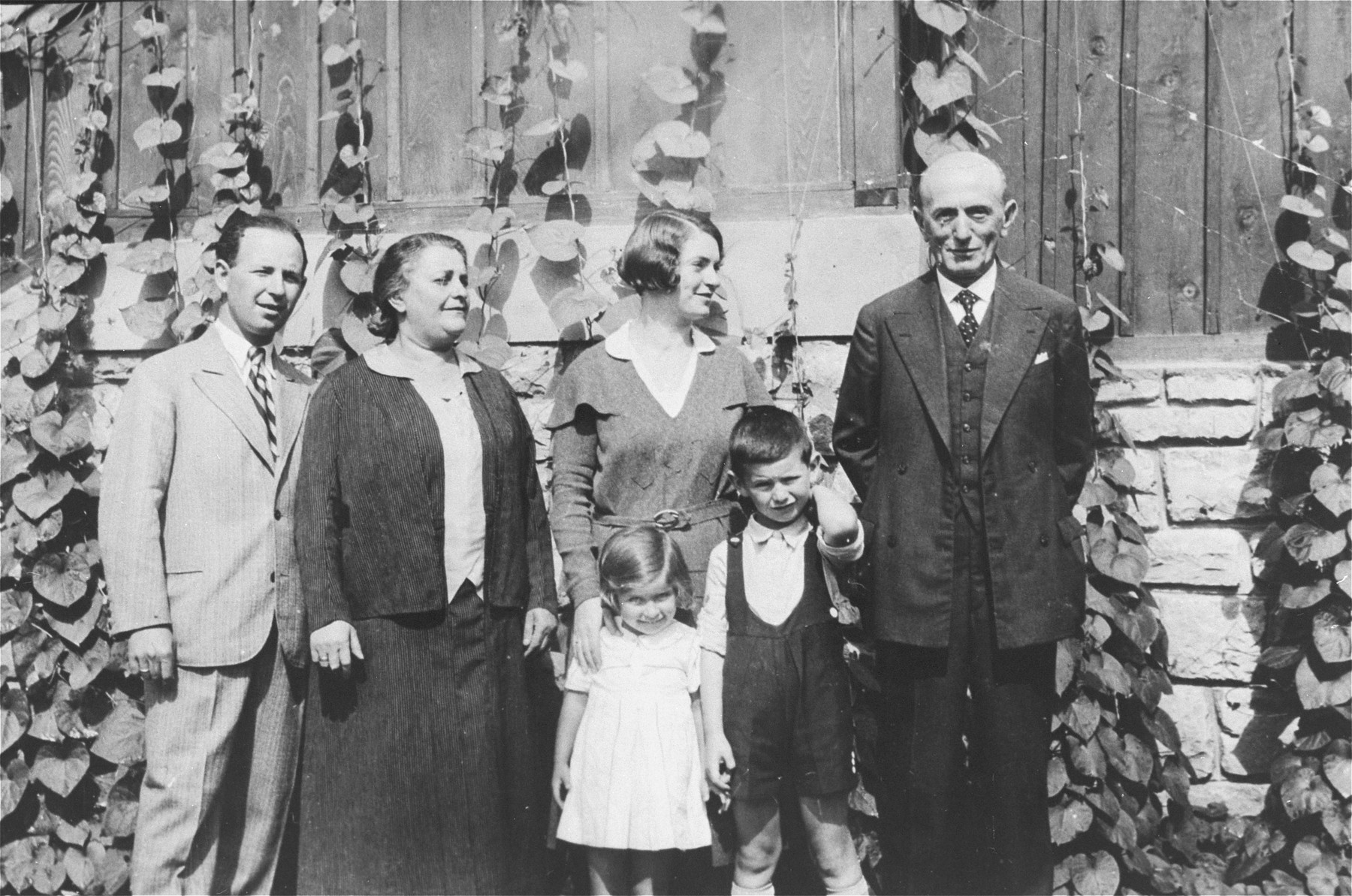 Portrait of a Yugoslav Jewish family living in Romania.  Pictured in front are Marta and Aurel Kupfermann.  Standing behind from left to right are: Beno Kupfermann, Rosa Klein, Blanka Kupfermann, and Julius Klein.