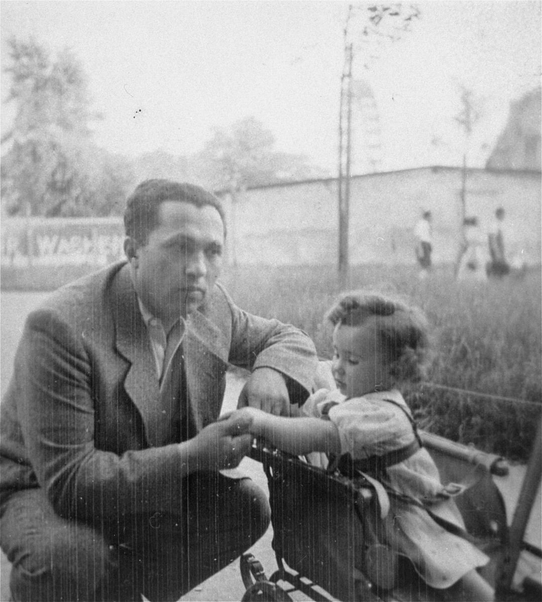 A Jewish father crouches next to his young daughter in a stroller.  Pictured are Dr. Gerson Reif with his two-year-old daughter, Liane.