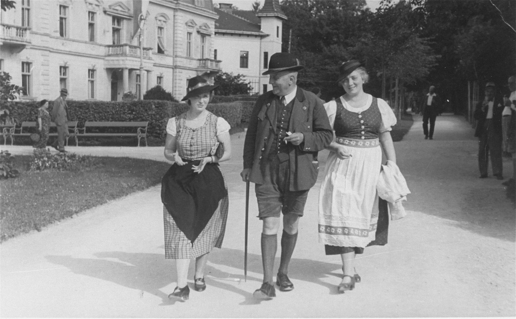 Three Jews dressed in traditional Austrian folk costume walk along a street in the resort town of Bad Hall.  Pictured are Klara Kafka (left) and Grete Woltar (right), the donor's half-sister.