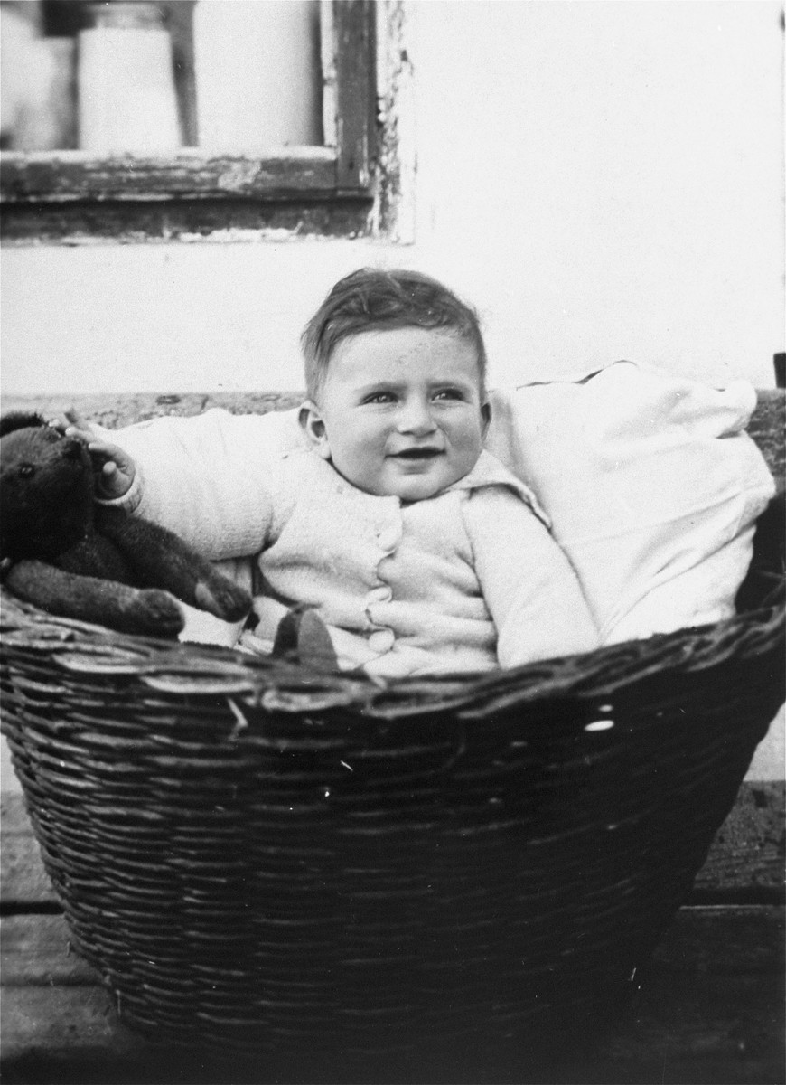 A young Jewish boy sits outside in a wicker basket in Osijek, Croatia.  Pictured is Lugo Szego, the son of Armin and Melanka (Gruenwald) Szego.  He perished with his parents during the Holocaust.
