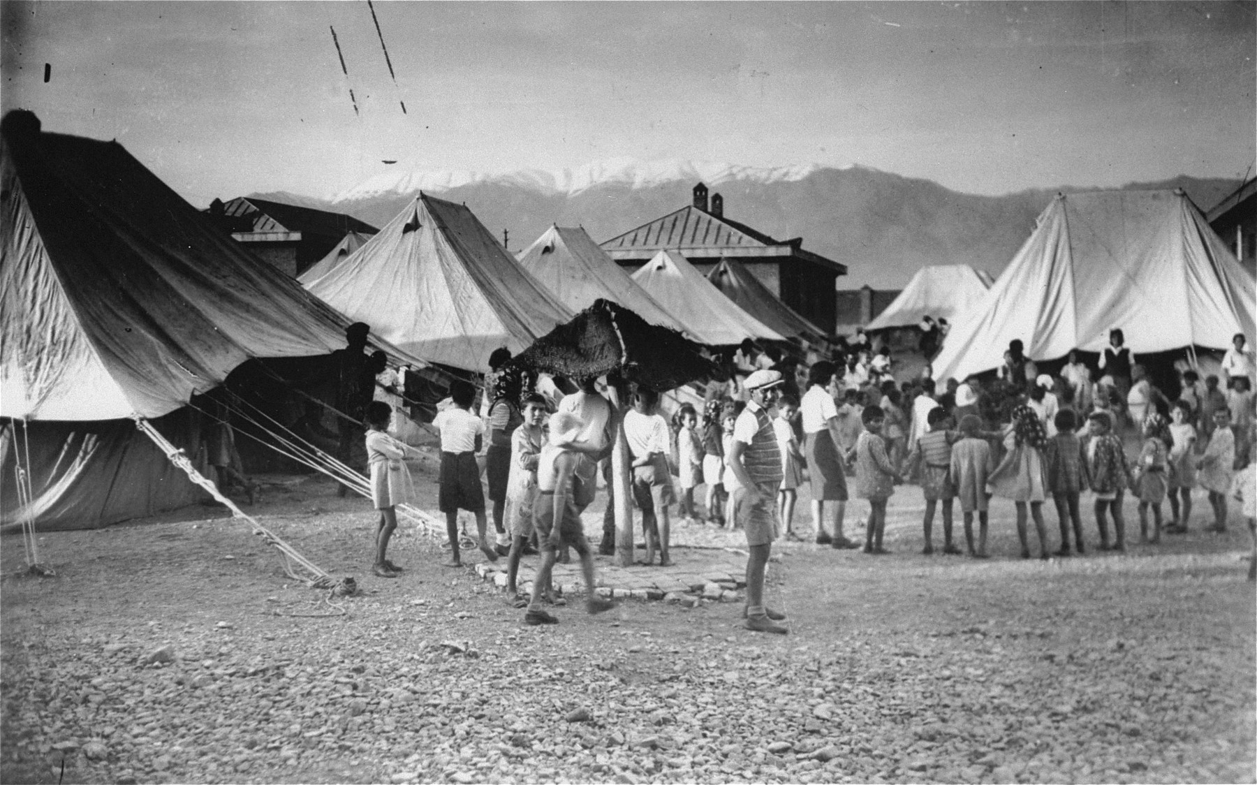 Members of the Teheran children's transport are gathered in front of tents at a refugee camp in Teheran.