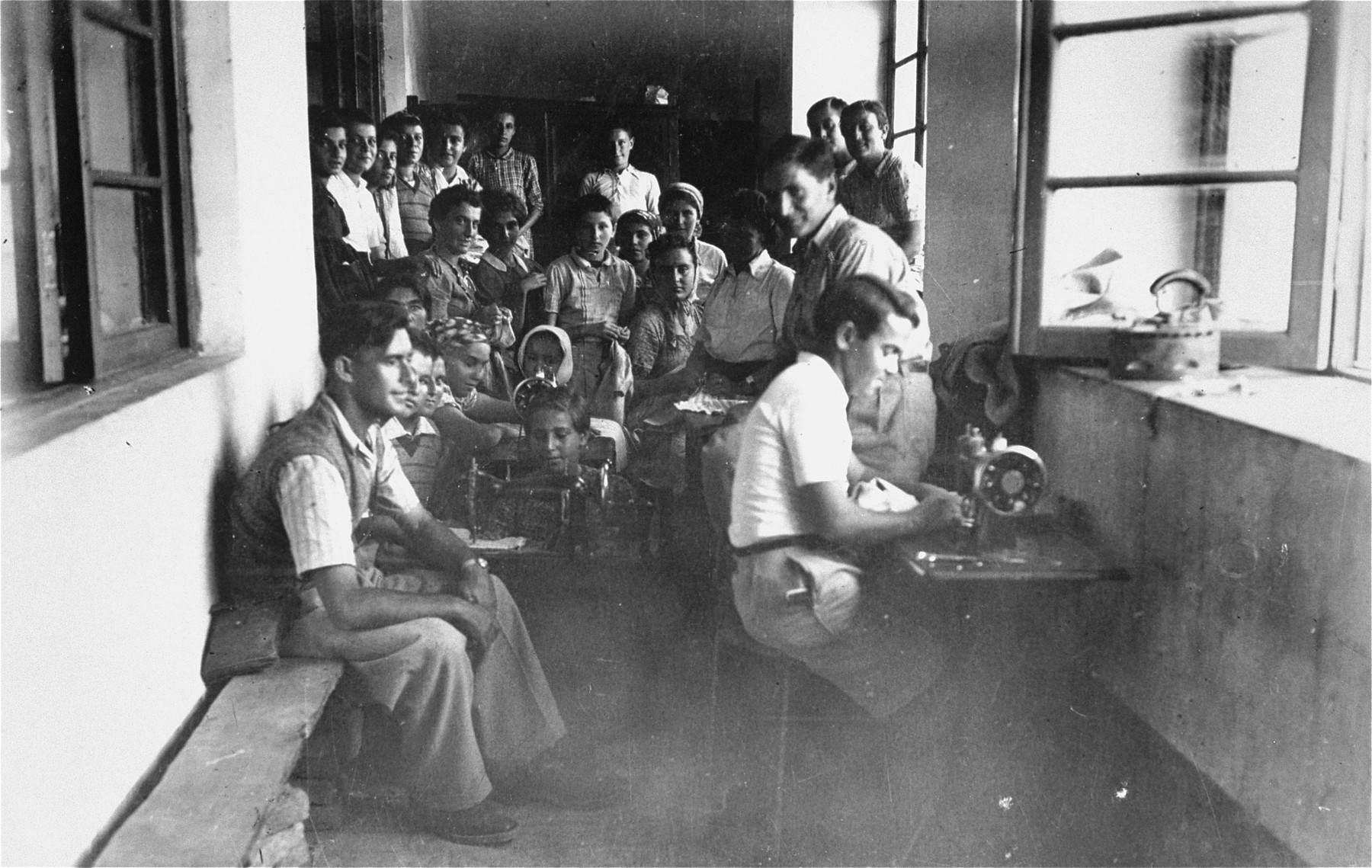 Members of the Teheran children's transport participate in a tailoring workshop at the refugee camp in Teheran.  Among those pictured are: David Laor (seated on the bench at the left) and Israel Goldstein (seated at the sewing machine).