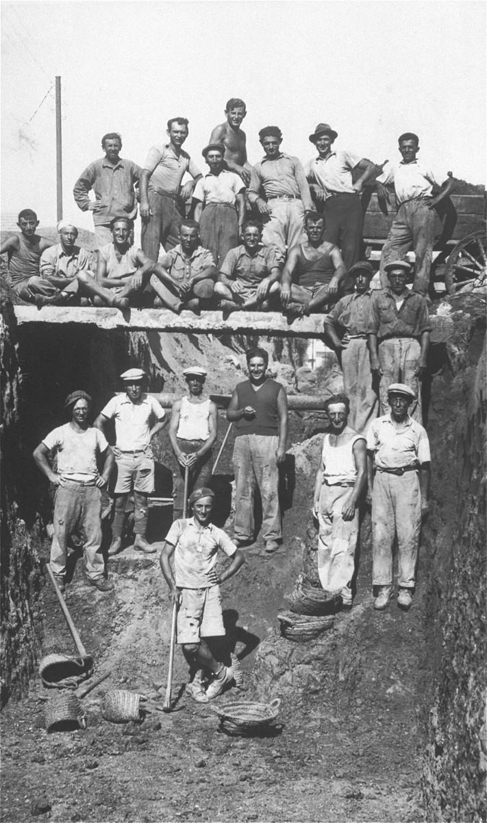 Group portrait of the employees of a construction company owned by David Saleschütz, an immigrant from Kolbuszowa, Poland.   David Saleschütz is pictured in the top row, second from the right. The laborers are laying the foundations for the Beit Sokolov building in Tel Aviv.