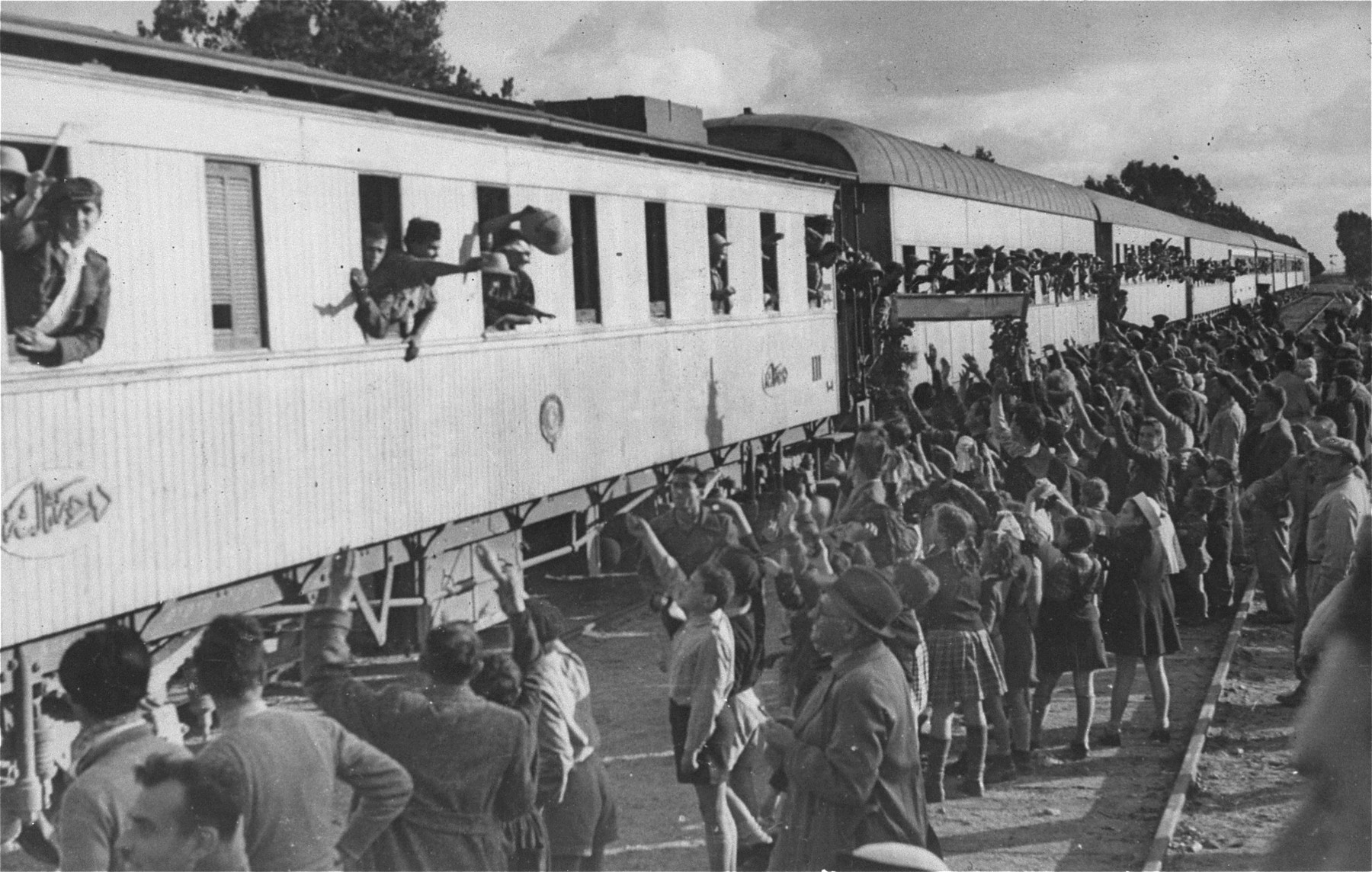 Members of the Yishuv (Jewish community in Palestine) greet the Teheran children as they arrive by train in Palestine.
