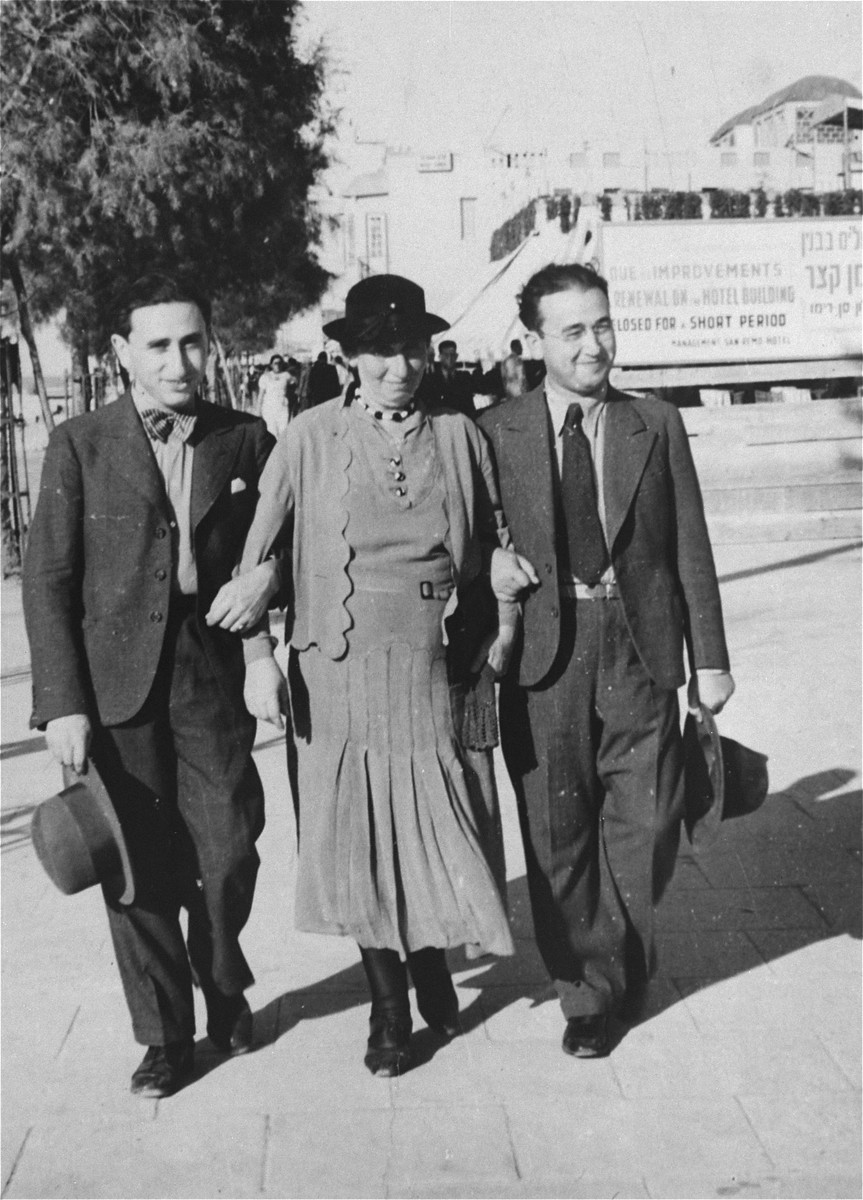 New immigrants from Poland walk along the street in Tel Aviv.  Pictured from left to right are Philip, Rivka and Yosef Genger.