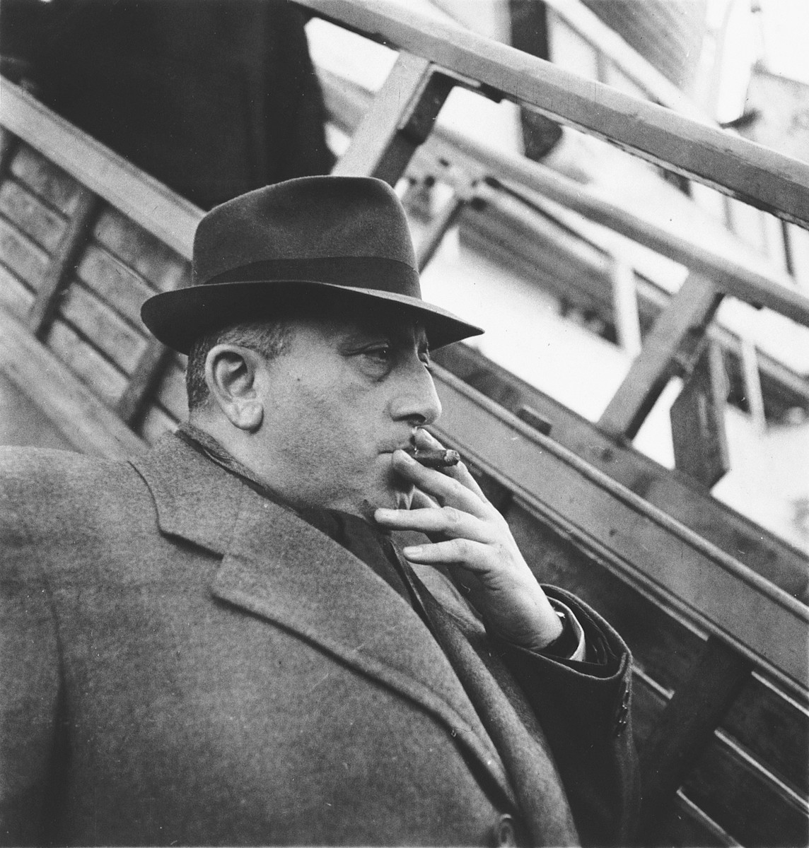 Albert Nussbaum, director of Transmigration for the American Joint Distribution Committee, smokes a cigar while waiting next to the gangway of the SS Serpa Pinto.