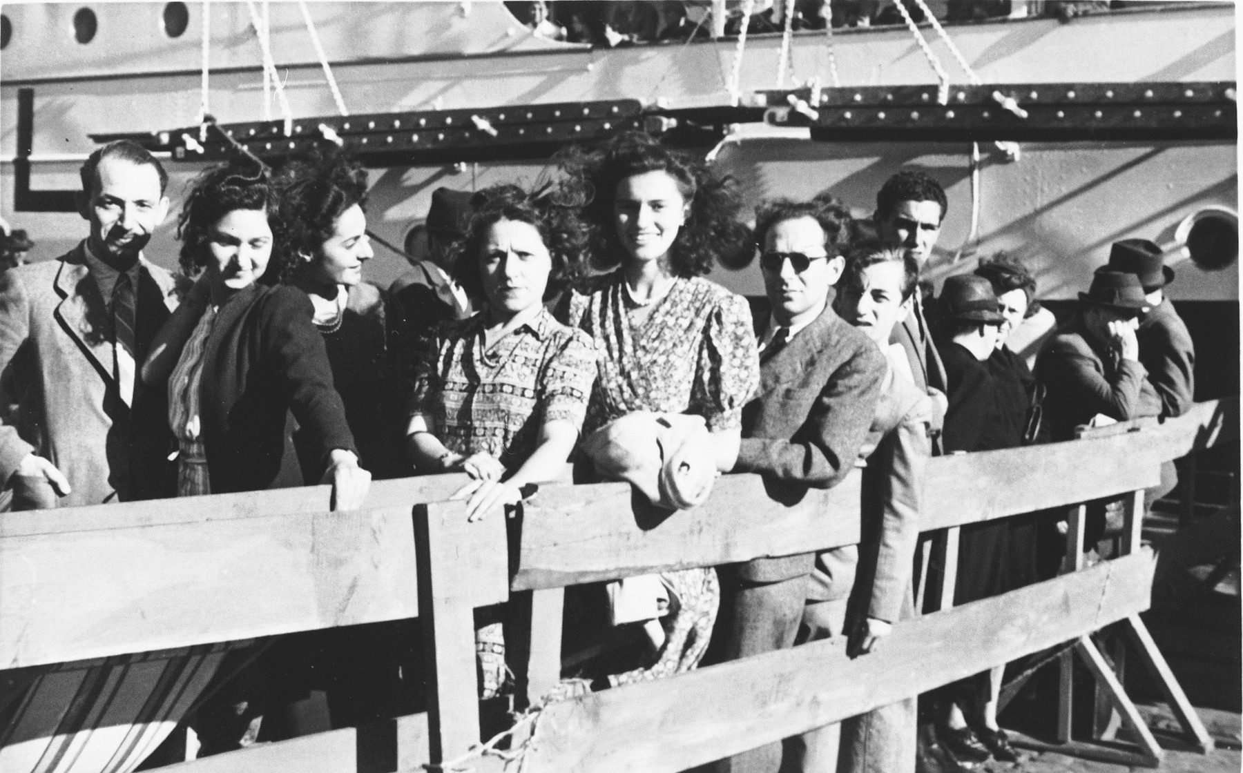 A group of Jewish refugees wait behind a wooden fence in the port of Lisbon before boarding the SS Mouzinho.