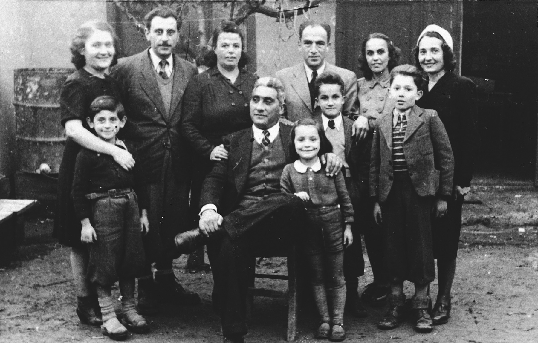Group portrait of Jewish refugee families from Yugoslavia who have fled to Tirana, Albania.  Among those pictured are Majer and Mimi Altarac (top row, fourth and fifth from the left) and their son, Jasa (in front of Majer), and Mosa and Gabriela Mandil (top row, first and second on the left), their son, Gavra (in front of Gabriela), and daughter Irena (front row, center).
