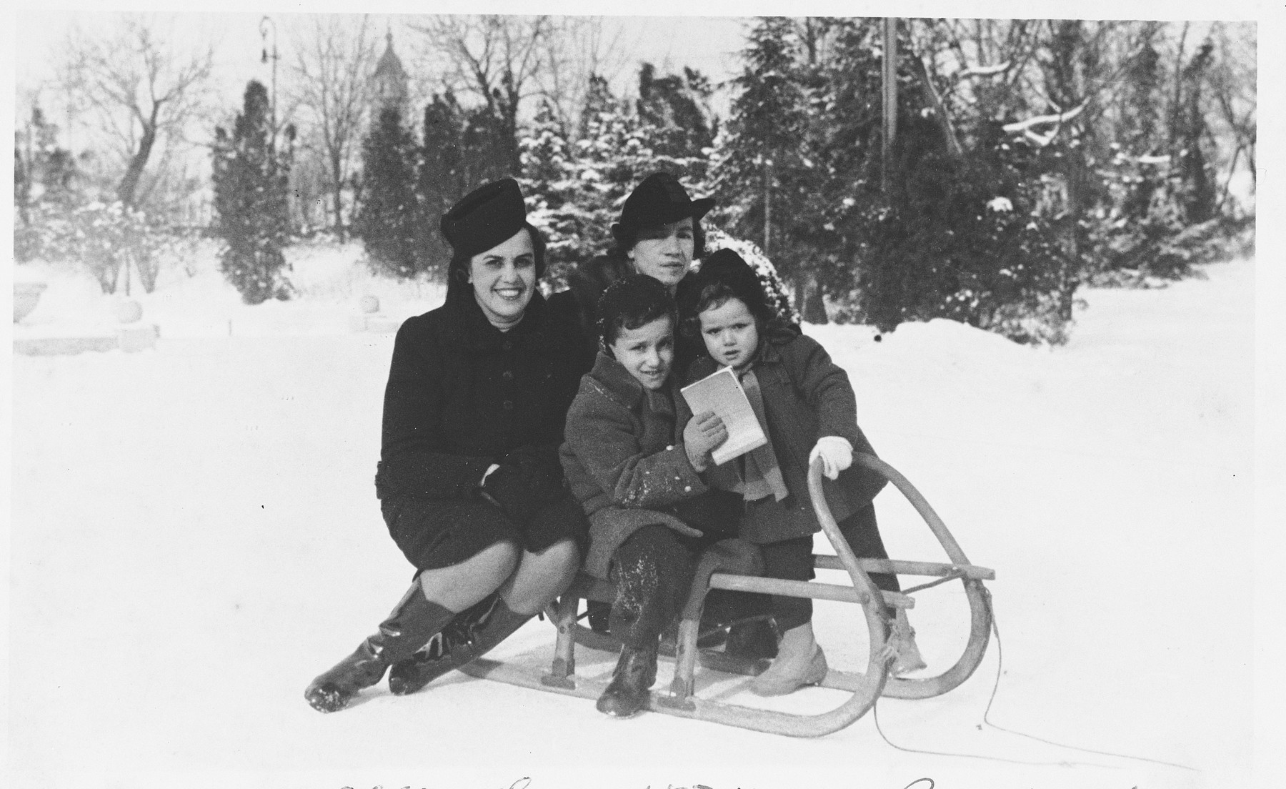 A Jewish family poses outside in the snow on a sled.  Pictured are Mimi Altarac (left) with her children, Jasa and Lela, and a female friend or relative.