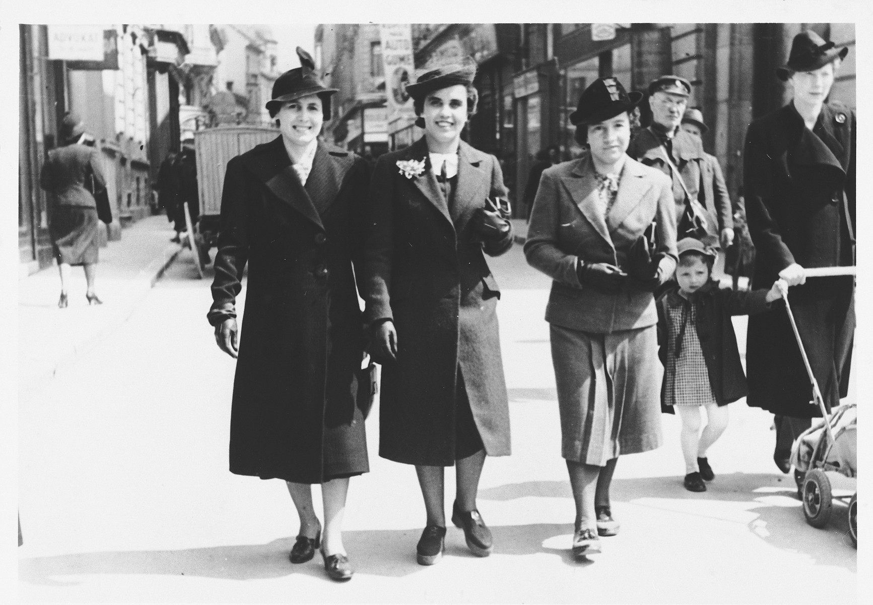 Three Jewish women walk along a commercial street in Sarajevo.  Among those pictured is Mimi Altarac (center).