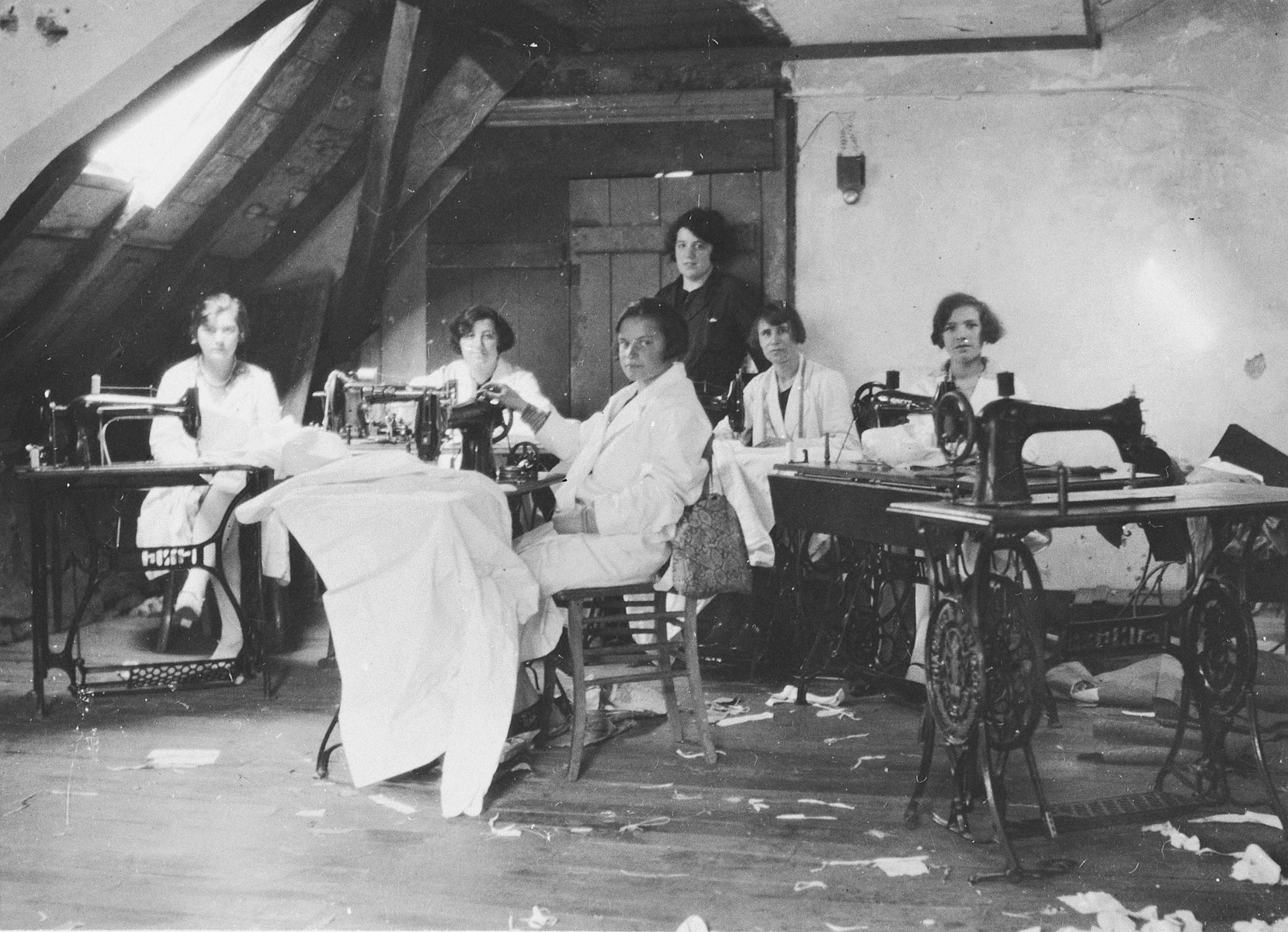 A group of young female employees pose at their sewing tables in the Palais d'Habillement clothing company in Luxembourg.  Among those pictured are Marquerite Nussbaum (standing at the back) and her sister Madeline (probably seated, second from the left).