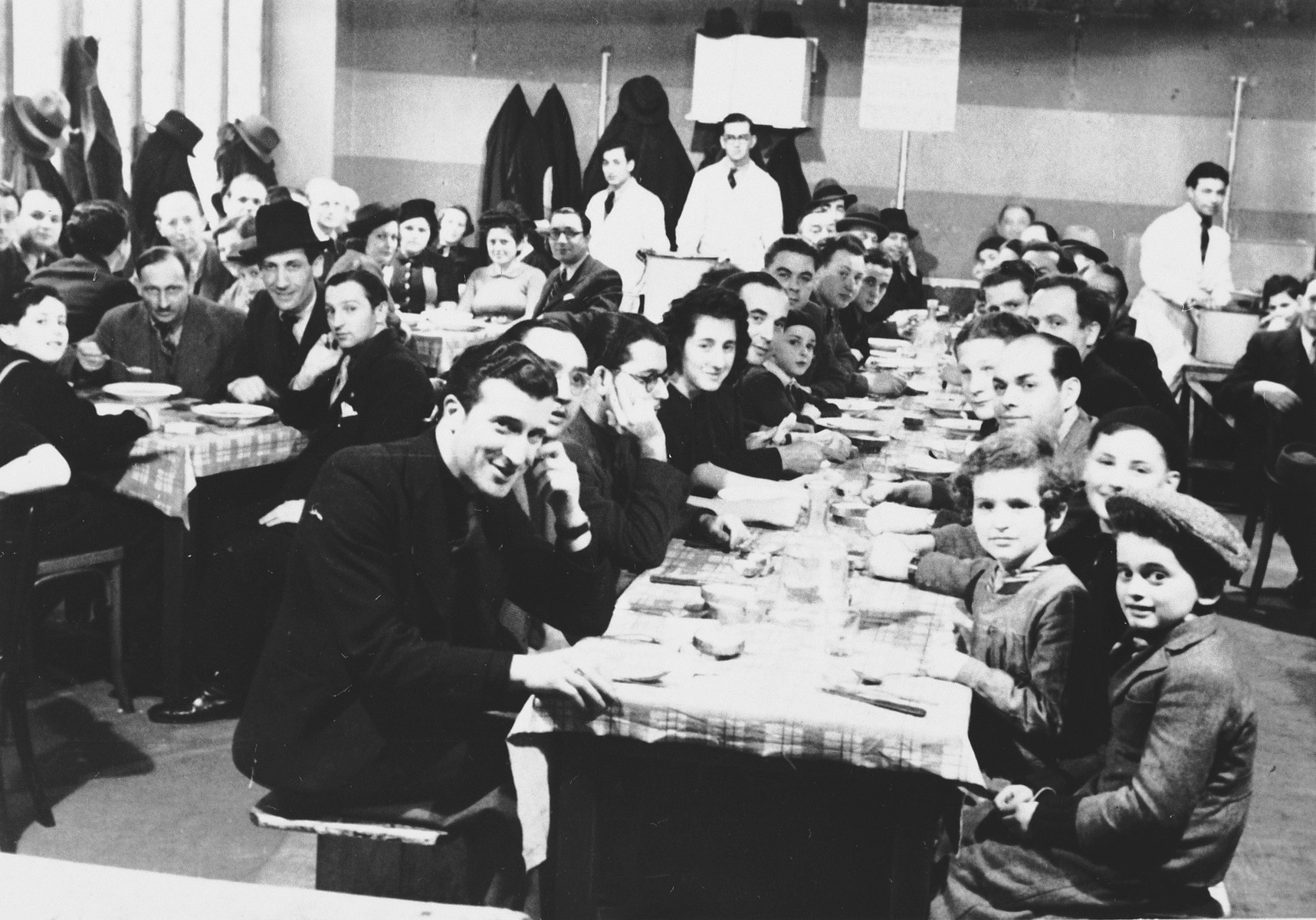 Jewish refugees from the Third Reich eat a meal in the dining hall of a refugee center in Luxembourg sponsored by the ESRA Jewish social welfare organization.