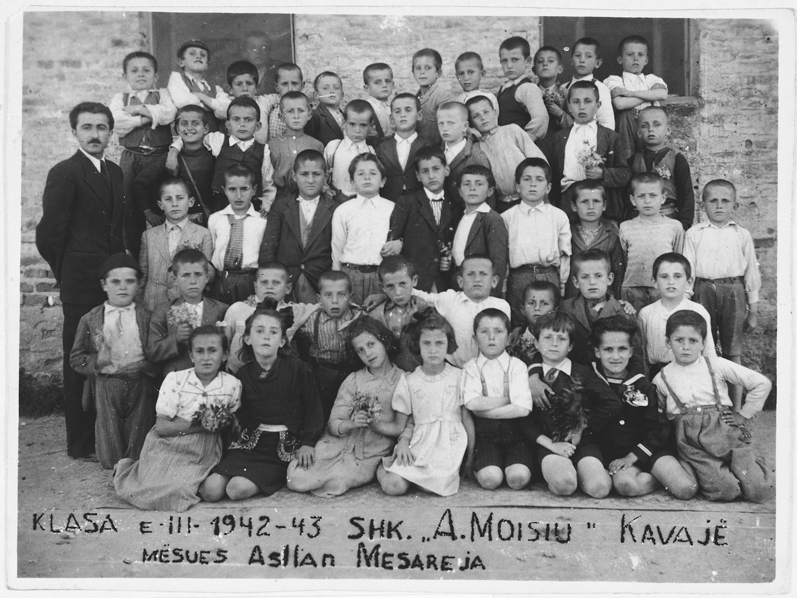 Group portrait of students at an elementary school in Kavaja, Albania.  Among the students are several Jewish refugee children from Yugoslavia.  Jasa Altarac is pictured in the front row, second from the right.