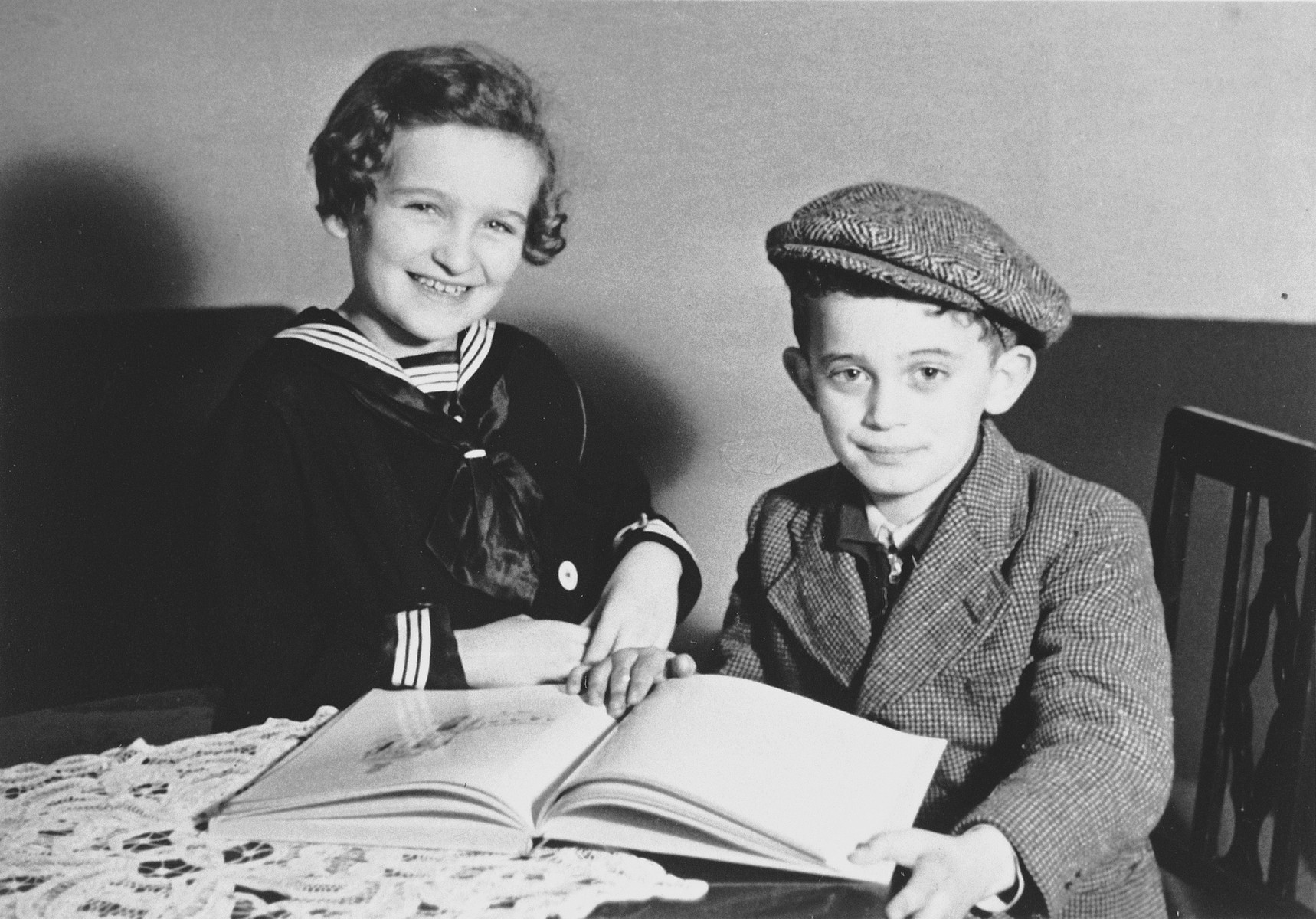 Two Jewish refugee children from the Third Reich who have resettled in Luxembourg and are being assisted by the ESRA Jewish social welfare organization, pose with an open book in their flat.