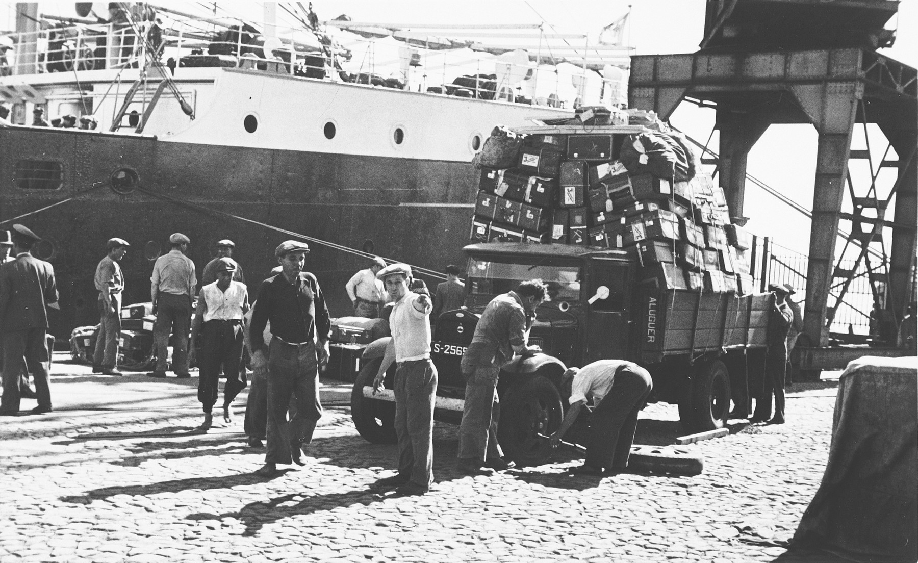 Portuguese dockworkers in the port of Lisbon prepare to transfer the luggage of Jewish refugees from a truck to the SS Mouzinho.