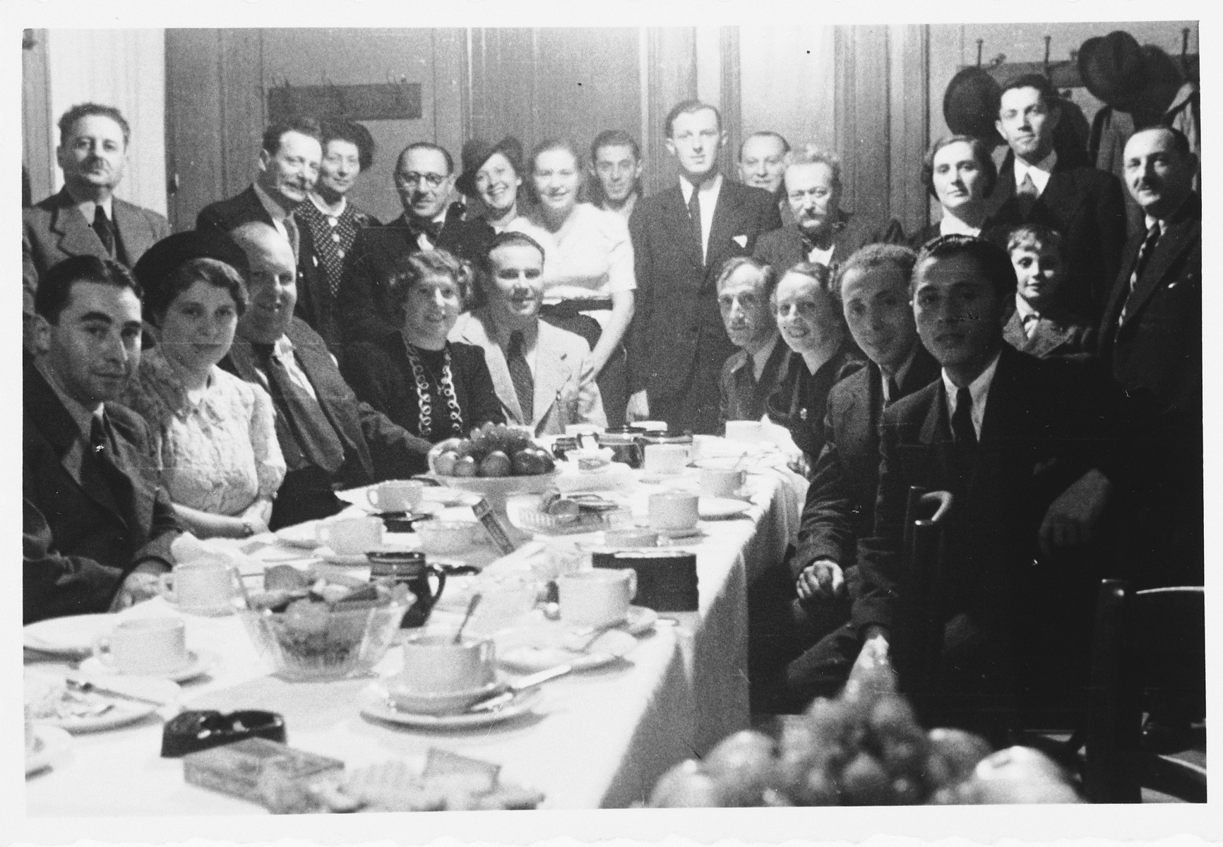Members of the Luxembourg Jewish community pose with Jewish refugees from the Third Reich around a long dining table at a gathering sponsored by the ESRA Jewish social welfare organization.