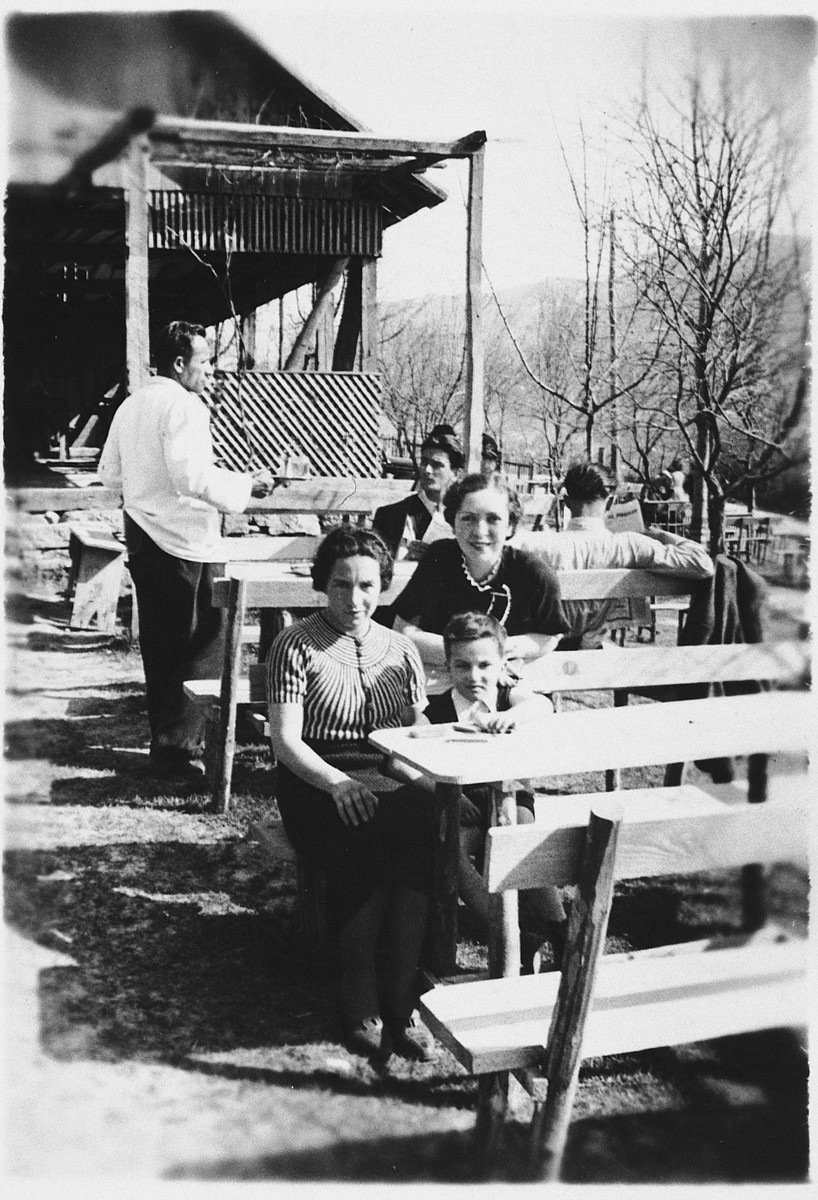 A Jewish mother and son sit at a table in an outdoor café in Sarajevo.  Pictured are Mimi and Jasa Altarac.